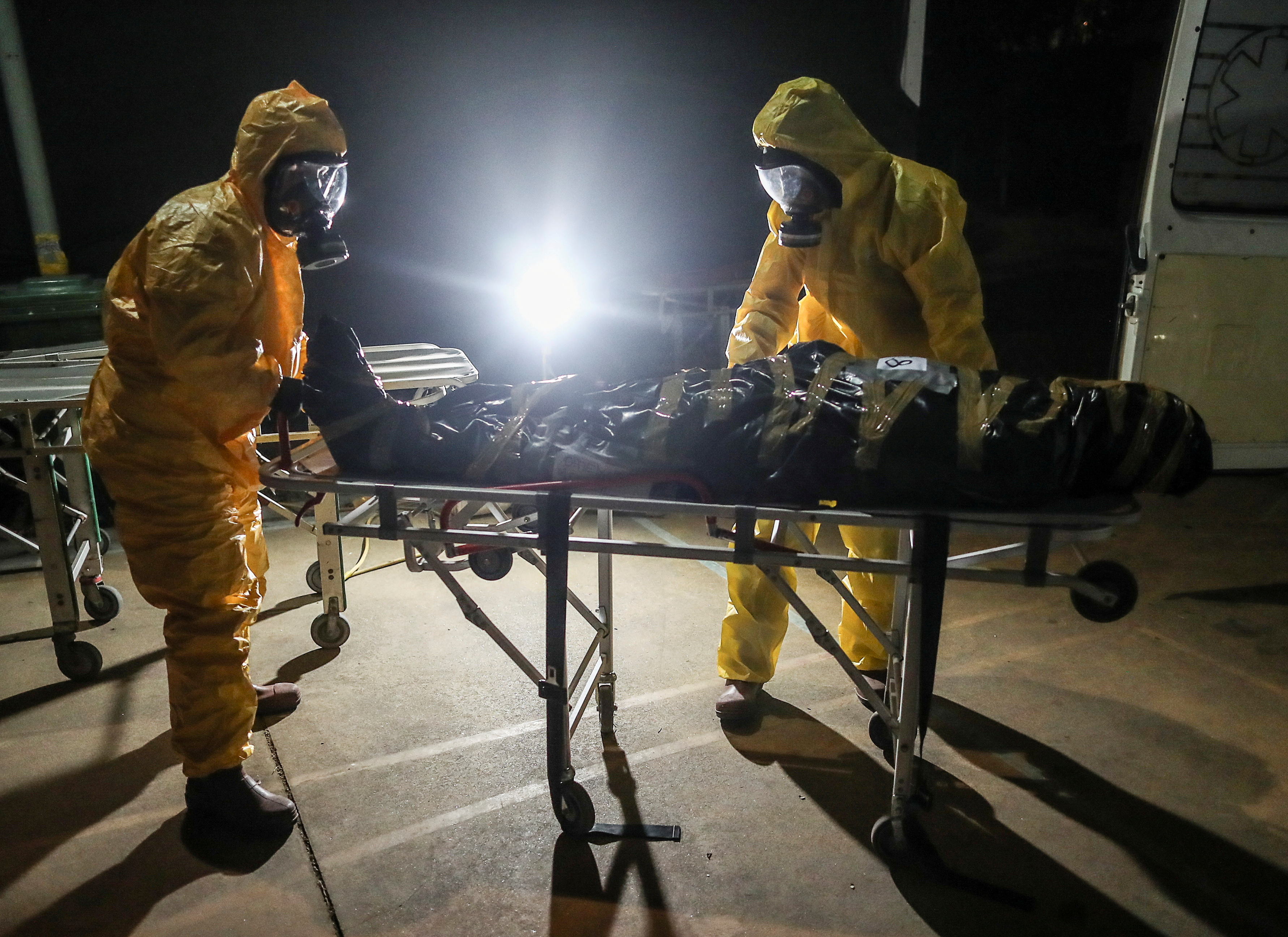 Gaston Rusichi and Oscar Oliva, members of the Department of High Risk Units (DUAR) push a stretcher with a body of a person who died from the coronavirus disease (COVID-19), at DUAR's headquarters, in Cordoba, Argentina, July 11, 2021. REUTERS/Agustin Marcarian/File Photo