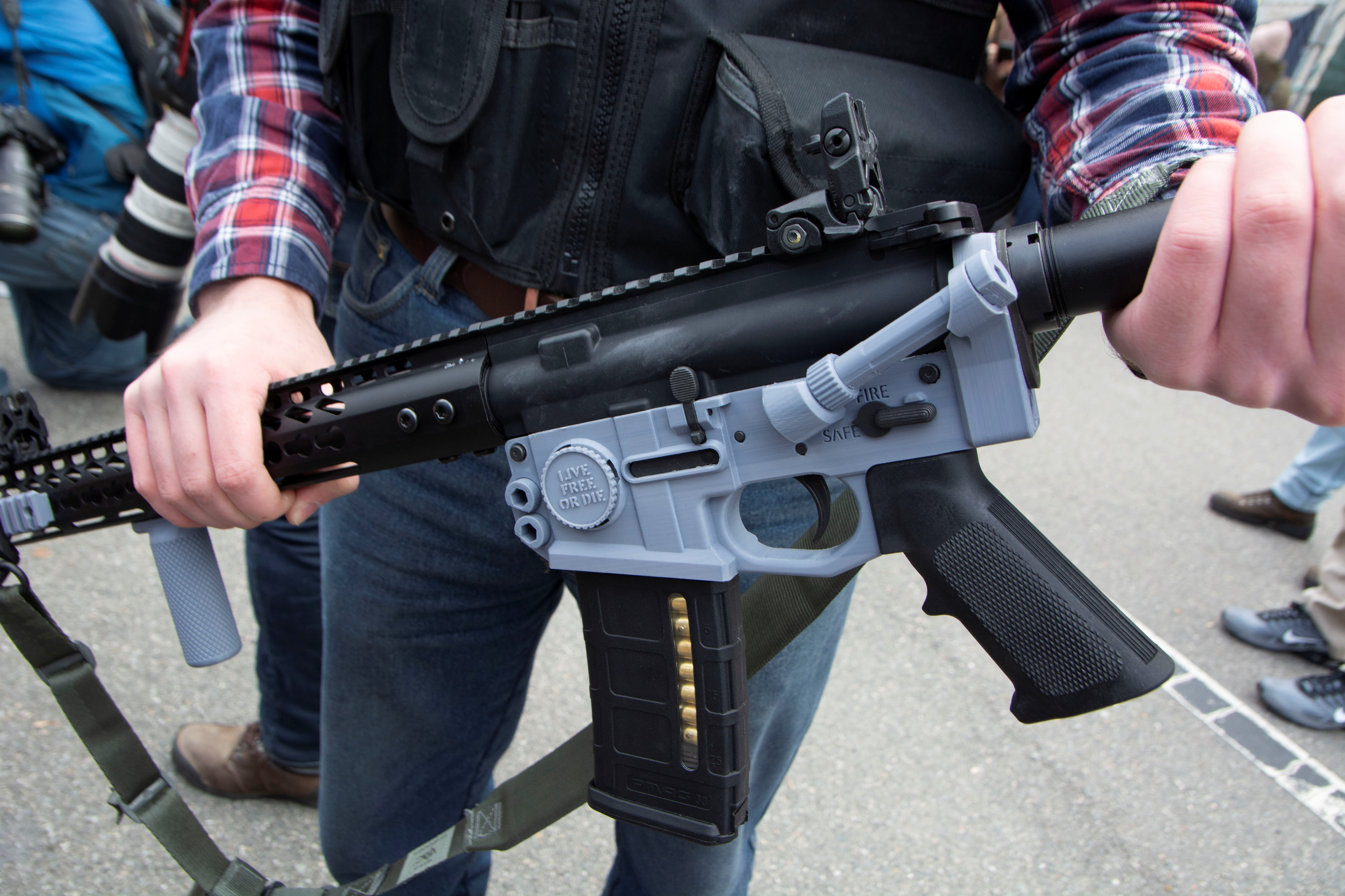 A participant in an armed rally shows a gun that has a 3D printed lower receiver, a weapon known as a