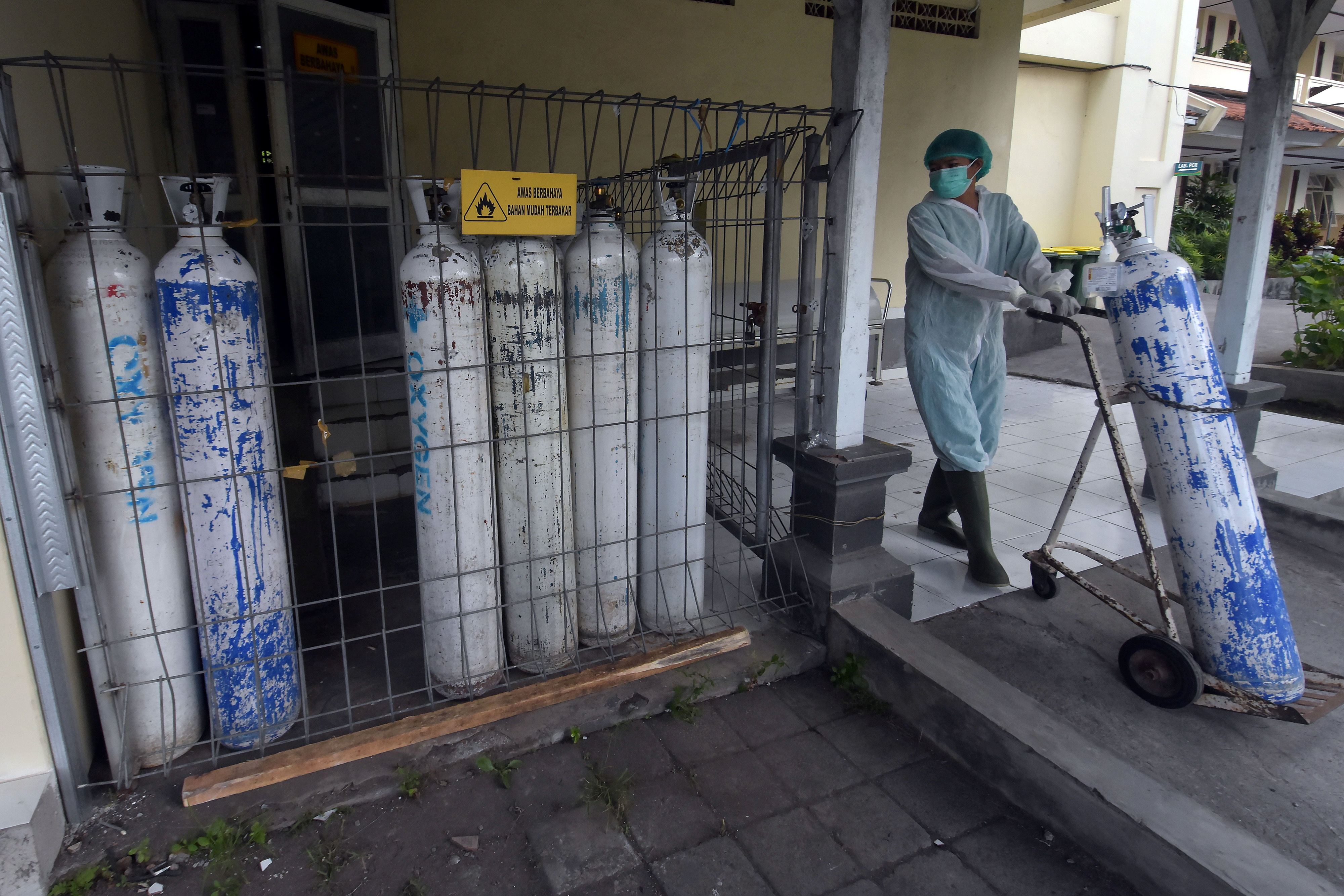 A medical worker pulls an oxygen cylinder to be delivered to the emergency ward at a government-run hospital amid the coronavirus disease (COVID-19) outbreak in Denpasar, Bali, Indonesia, July 23, 2021, in this photo taken by Antara Foto. Antara Foto/Nyoman Hendra Wibowo/ via REUTERS