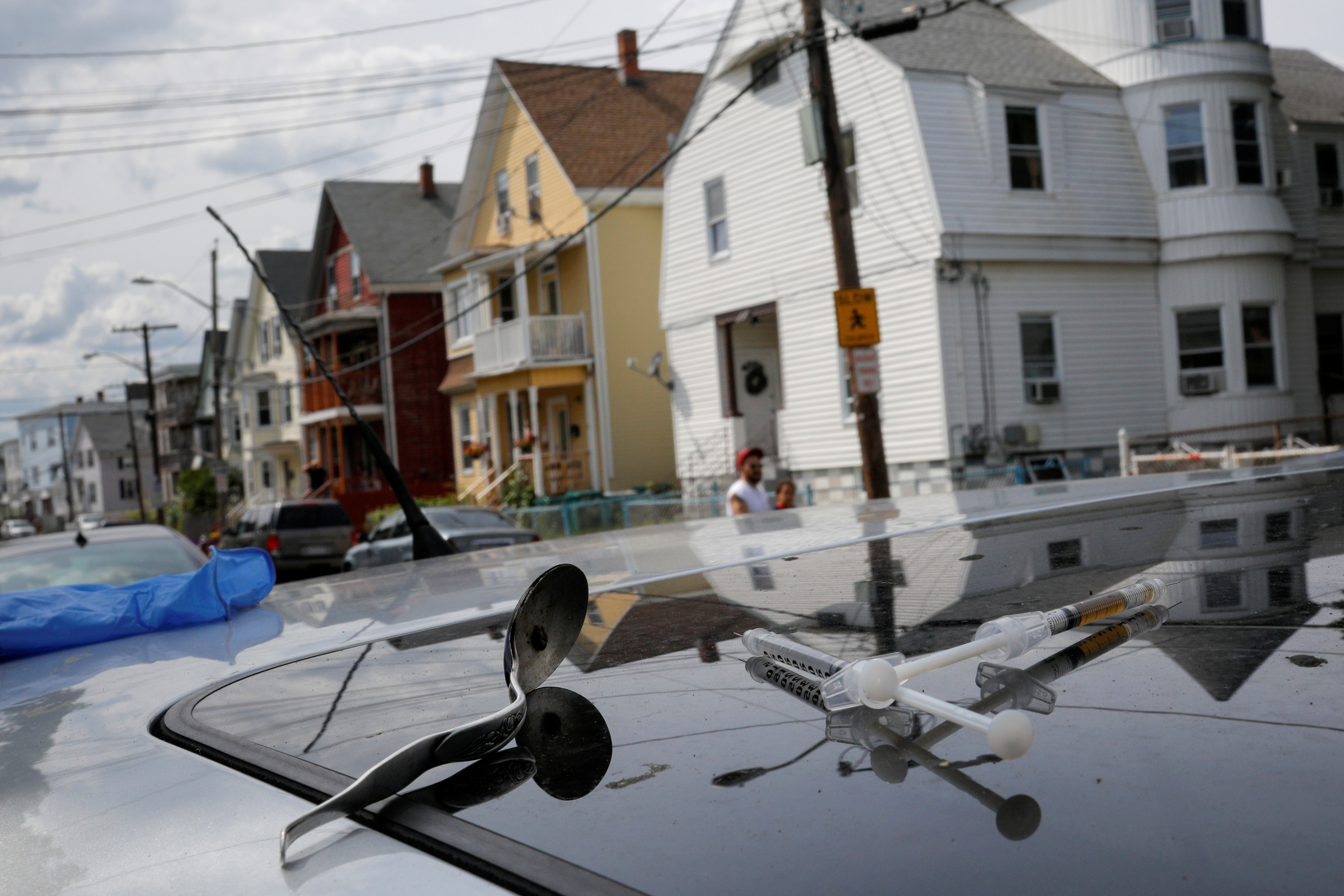 A full syringe, empty syringe and spoon sit on the roof of the car in which a man in his 20's overdosed on an opioid in the Boston suburb of Lynn, Massachusetts, August 14, 2017. REUTERS/Brian Snyder/File Photo