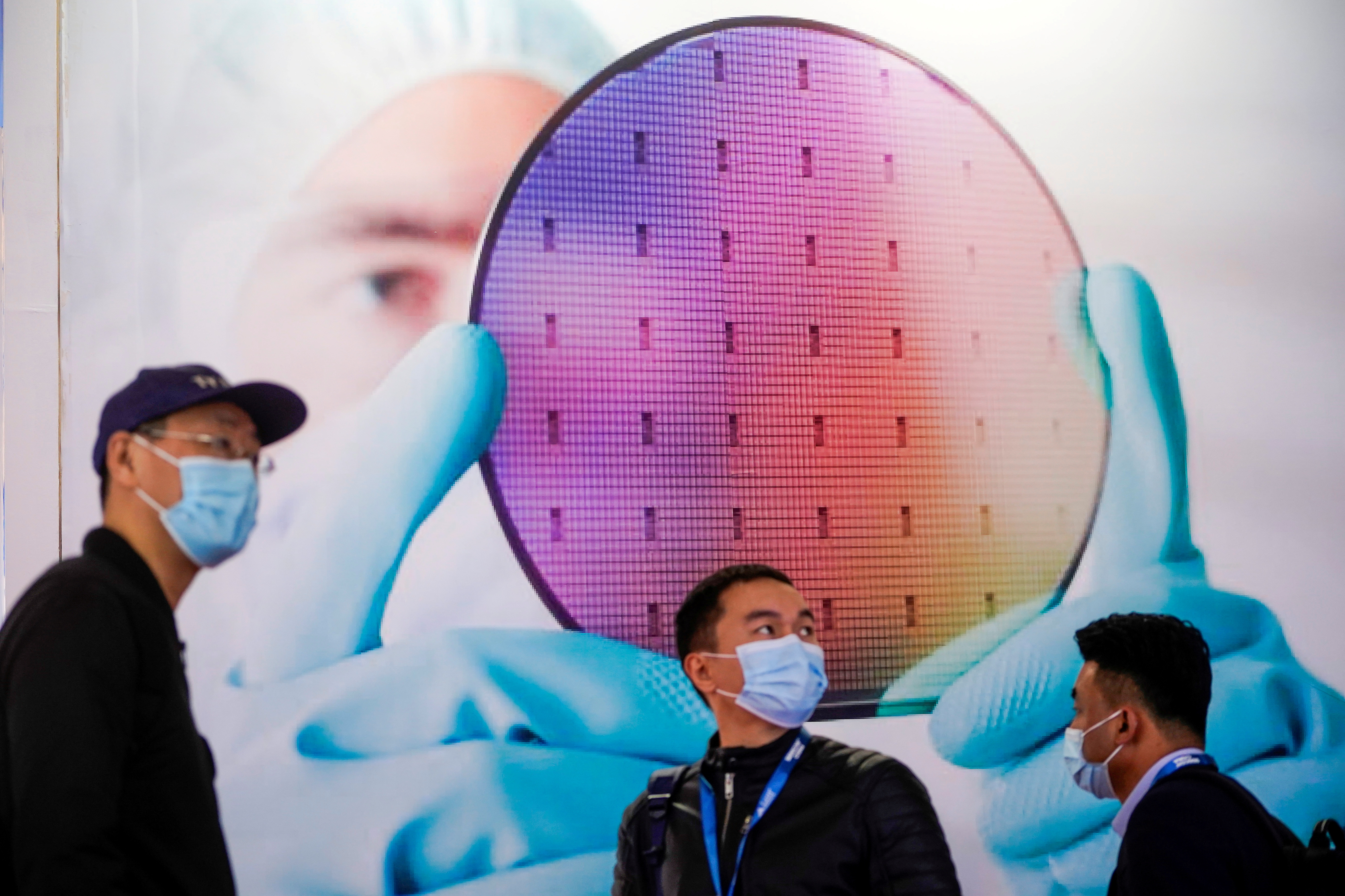 People visit a display of semiconductor device at Semicon China, a trade fair for semiconductor technology, in Shanghai, China March 17, 2021. REUTERS/Aly Song/File Photo