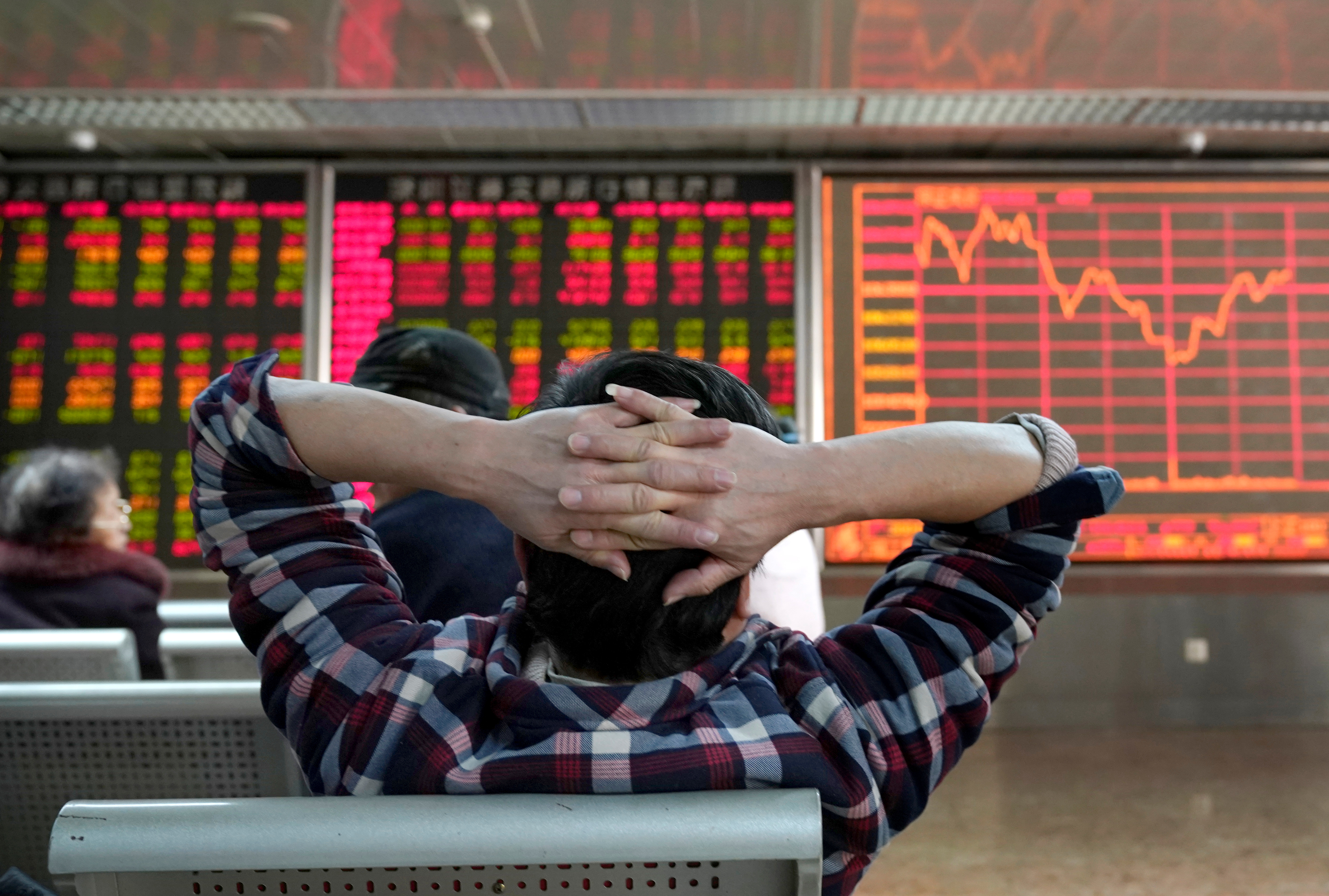An investor looks at a stock quotation board at a brokerage office in Beijing, China January 3, 2020. REUTERS/Jason Lee