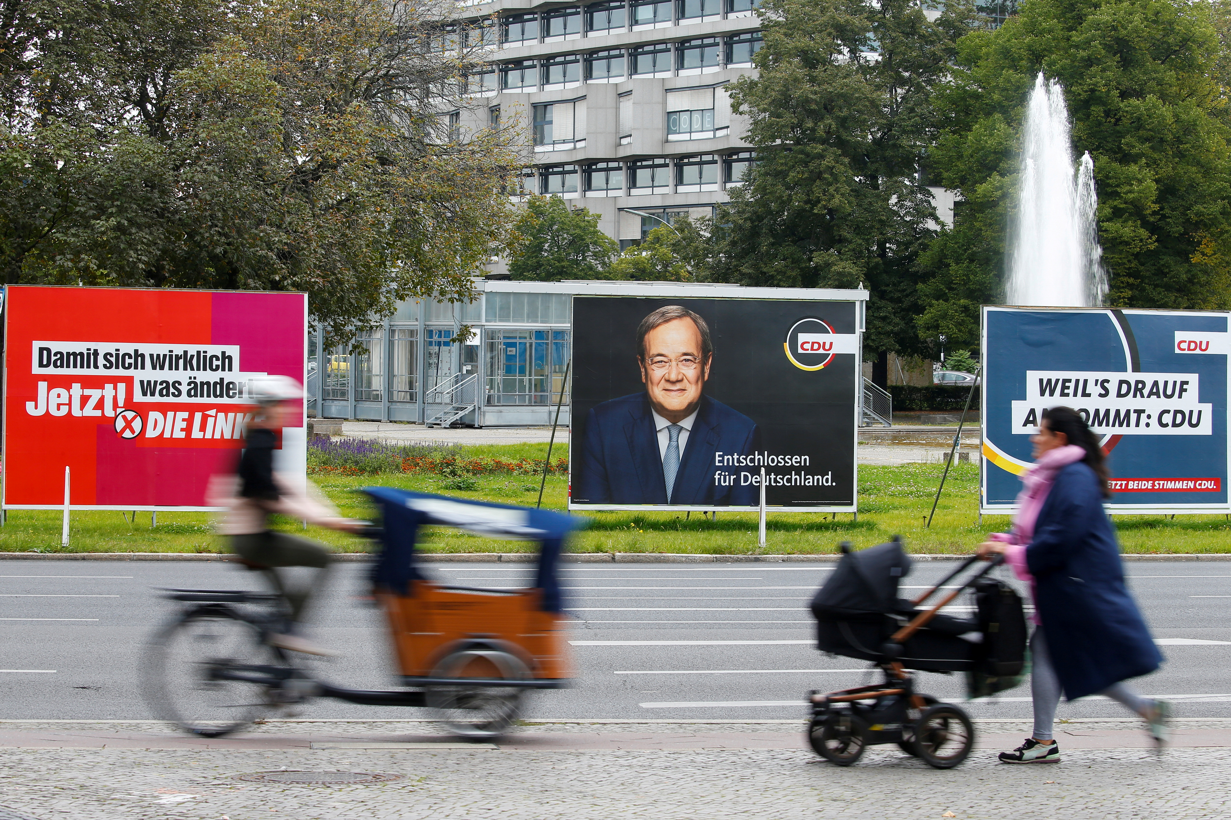 People pass by election campaign billboards featuring Christian Democratic Union (CDU) party leader and top candidate for chancellor, Armin Laschet, and the left wing party Die Linke, in Berlin, Germany, September 20, 2021. REUTERS/Michele Tantussi/