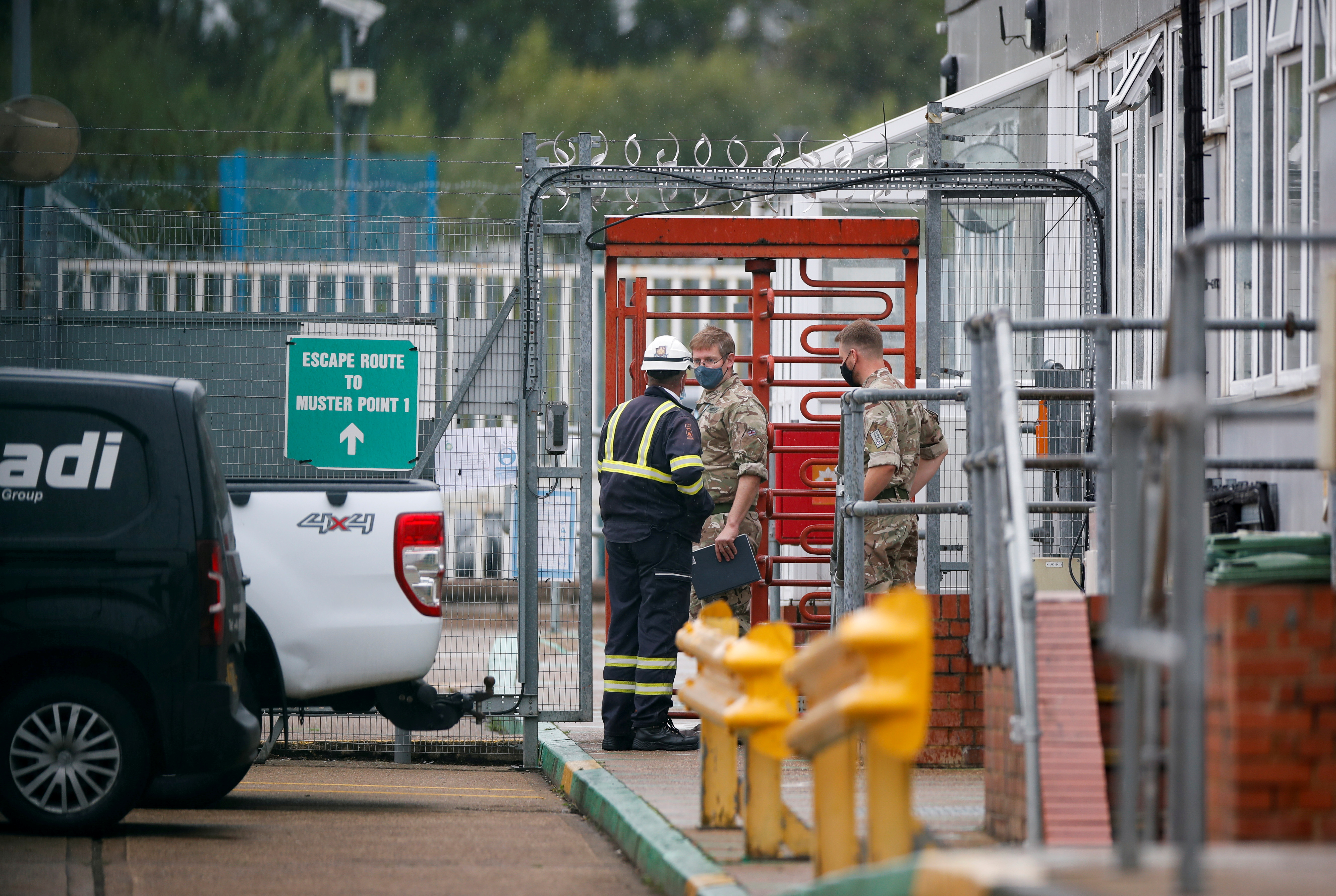 Members of the military speak to a worker at Buncefield Oil Depot in Hemel Hempstead, Britain, October 2, 2021. REUTERS/Paul Childs/File Photo