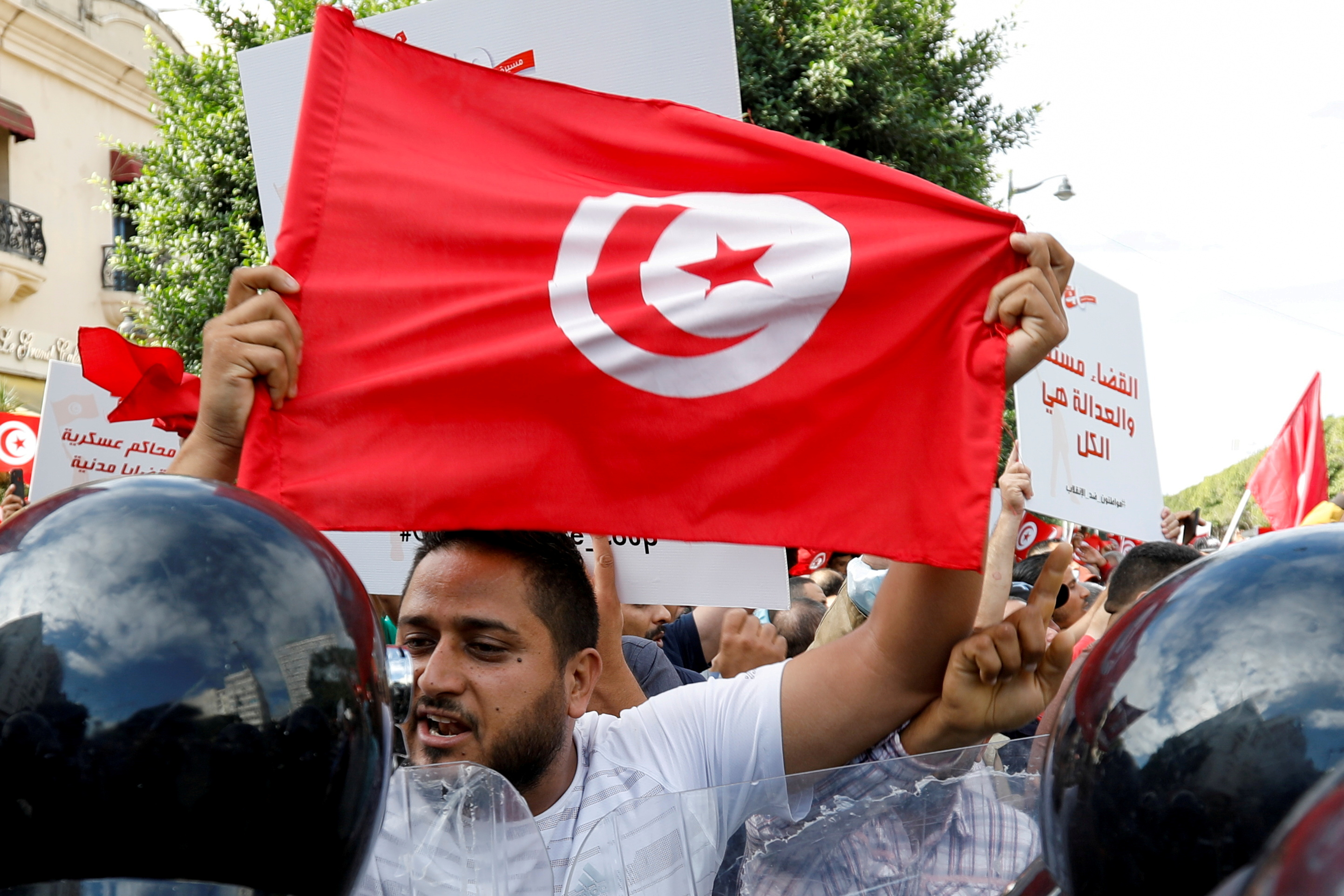 A demonstrator carries a Tunisian flag as he speaks with police during a protest against Tunisian President Kais Saied's seizure of governing powers, in Tunis, Tunisia, October 10, 2021. REUTERS/Zoubeir Souissi