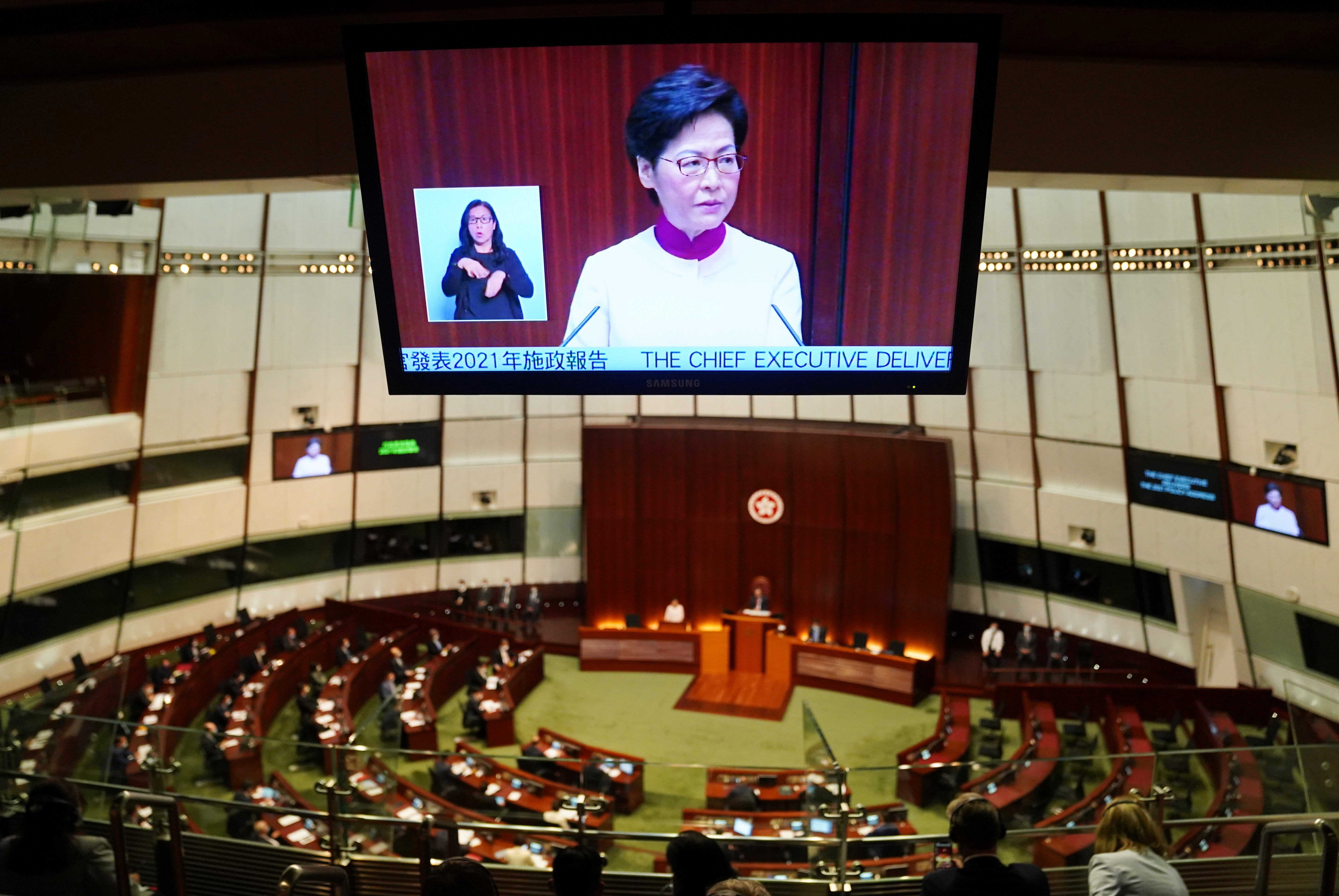 Hong Kong Chief Executive Carrie Lam is seen on a tv screen as she delivers her annual policy address at the Legislative Council in Hong Kong, China October 6, 2021. REUTERS/Lam Yik