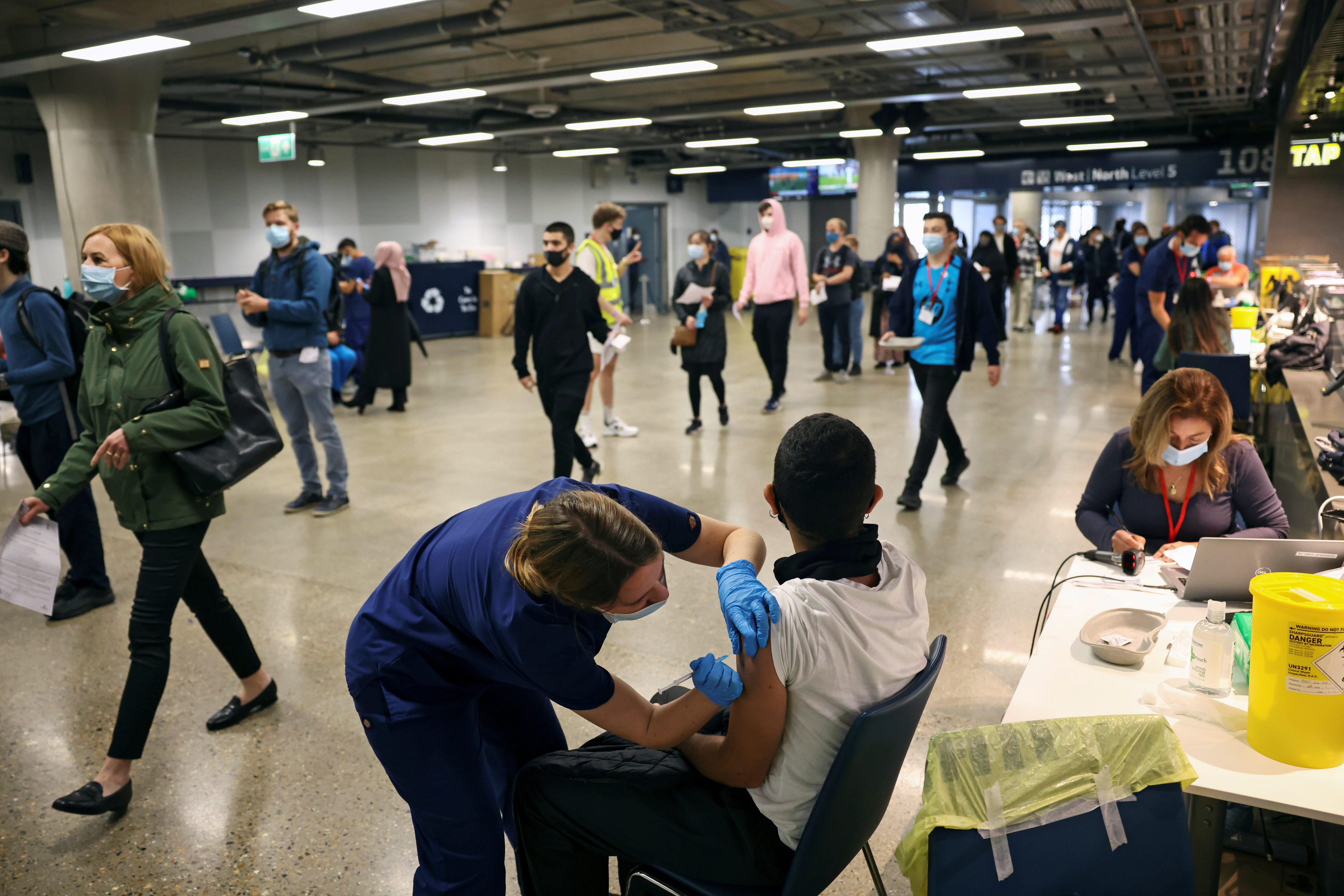 A person receives a dose of the Pfizer BioNTech COVID-19 vaccine at a mass vaccination centre for those aged 18 and over at the Tottenham Hotspur Stadium, amid the coronavirus disease (COVID-19) pandemic, in London, Britain, June 20, 2021. REUTERS/Henry Nicholls