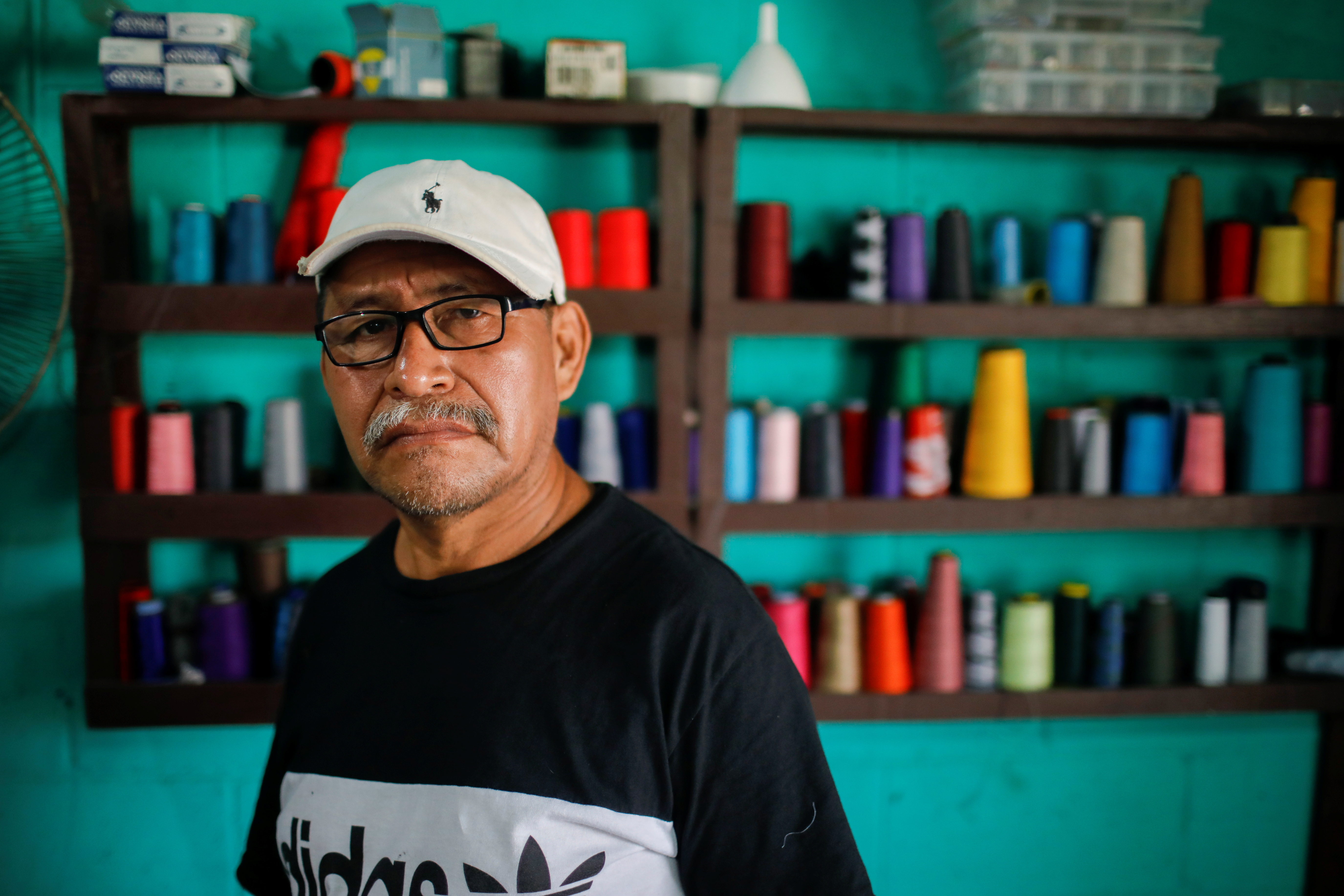 Jaime Ramirez, 60-year-old tailor who receives remittances from his daughters living in the U.S., talks with Reuters at his shop in Colon, El Salvador, September 3, 2021. REUTERS/Jose Cabezas