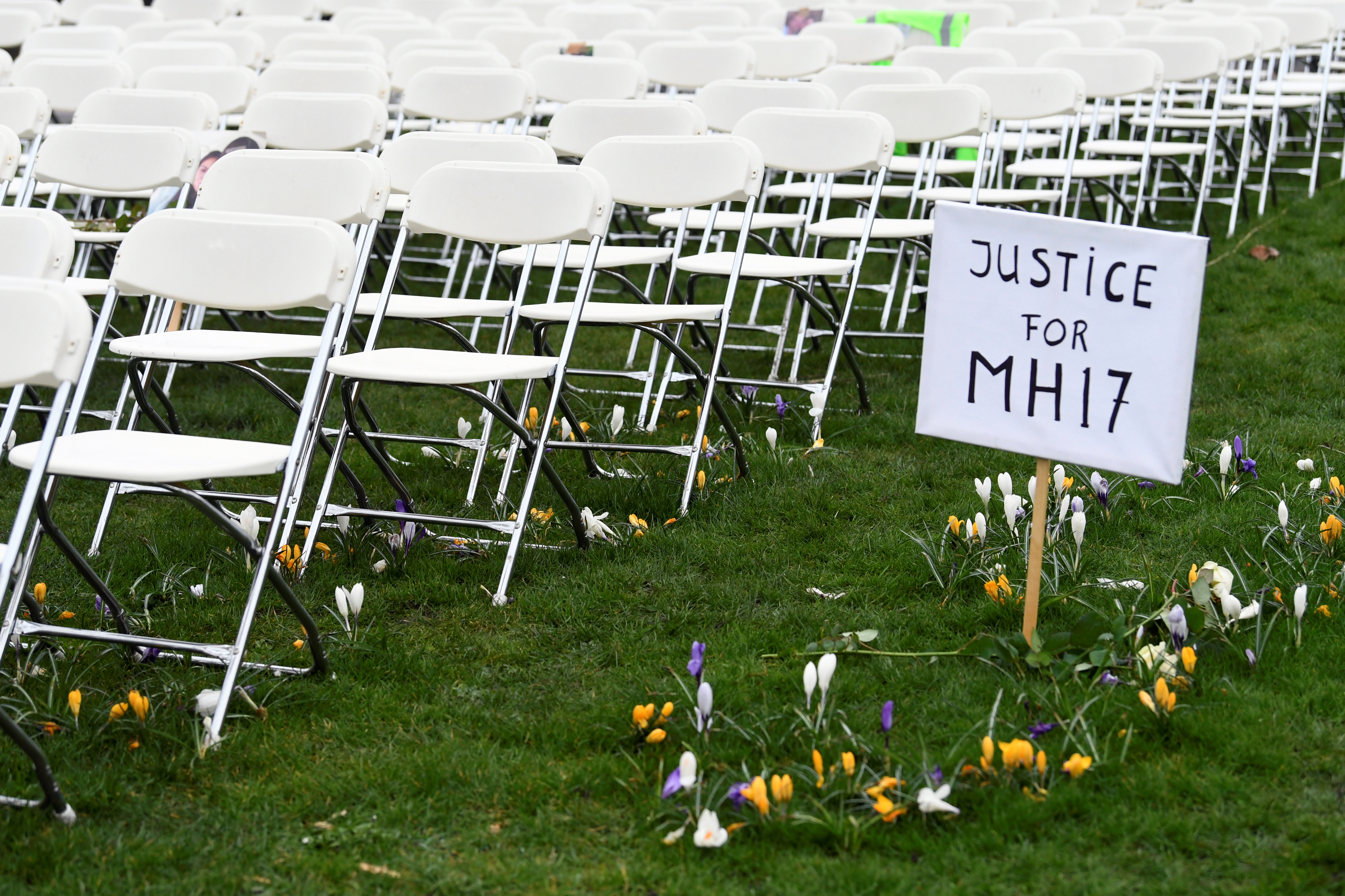 A protest sign stands next to rows of empty chairs, lined up by family members of victims of the MH17 crash line for each seat on the plane, during a protest outside the Russian Embassy in The Hague, Netherlands March 8, 2020.  REUTERS/Piroschka van de Wouw