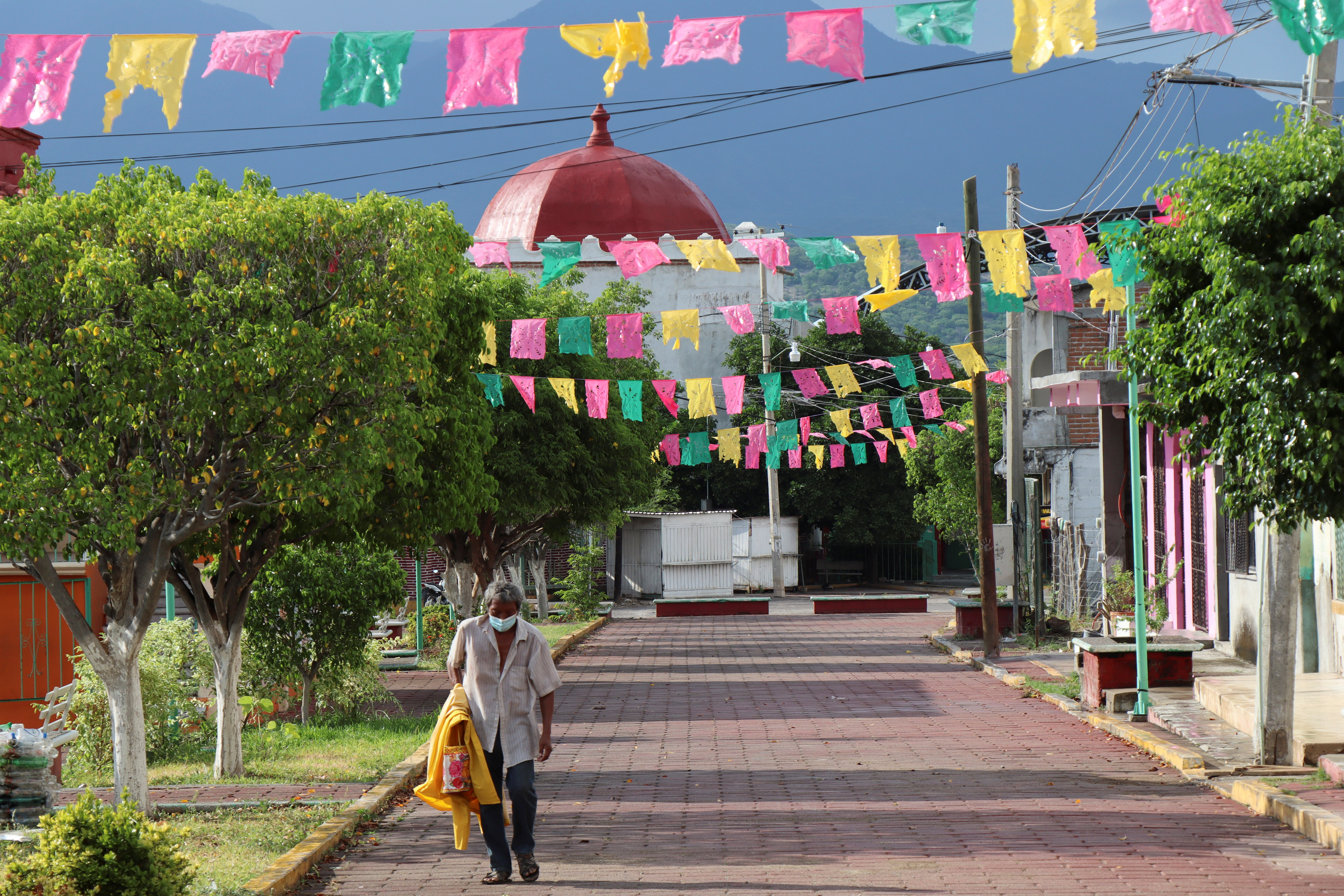 A man walks an empty street after authorities asked residents to stay at their homes, as the coronavirus disease (COVID-19) outbreak continues in the town of Magdalena Tequisistlan, in Oaxaca state, Mexico August 4, 2021. REUTERS/Jorge Luis Plata