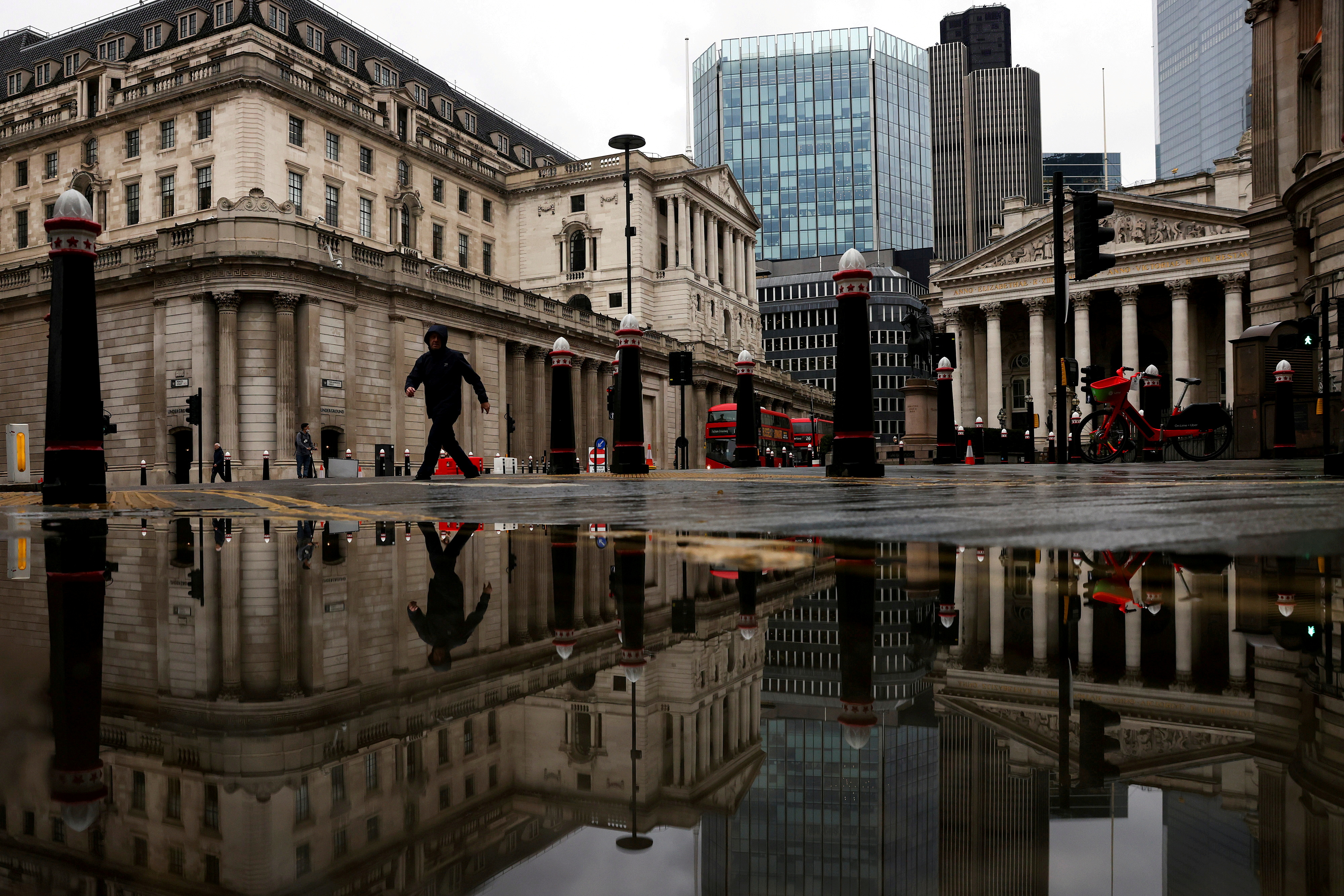 The Bank of England and Royal Exchange are reflected in a puddle as a pedestrian walks past, amid the coronavirus disease (COVID-19) outbreak in London, Britain, November 19, 2020. REUTERS/Simon Dawson/File Photo