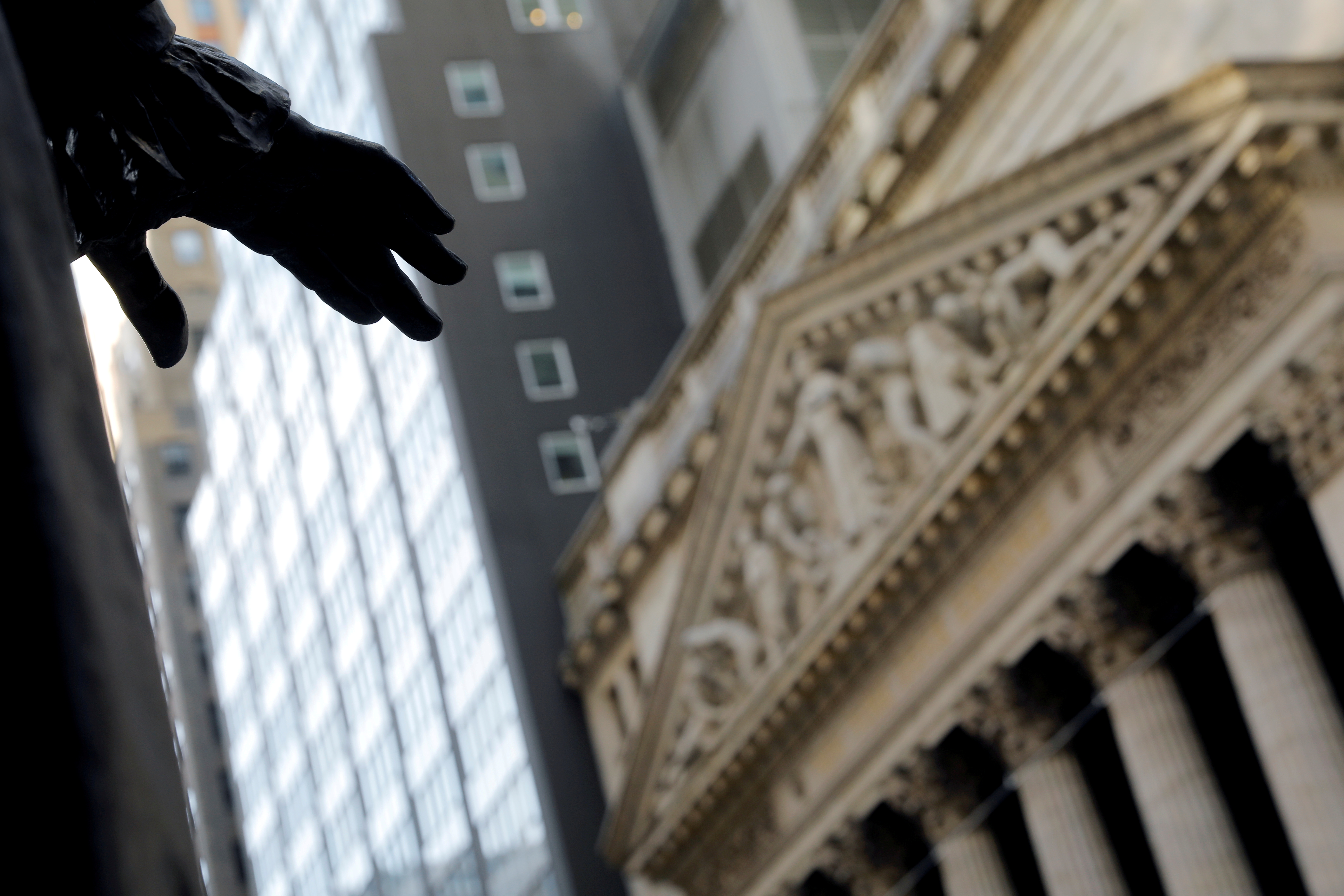 The hand of a sculpture of former U.S. President George Washington is pictured with the facade of the New York Stock Exchange (NYSE) in Manhattan in New York City, New York, U.S., January 28, 2021. REUTERS/Mike Segar/File Photo