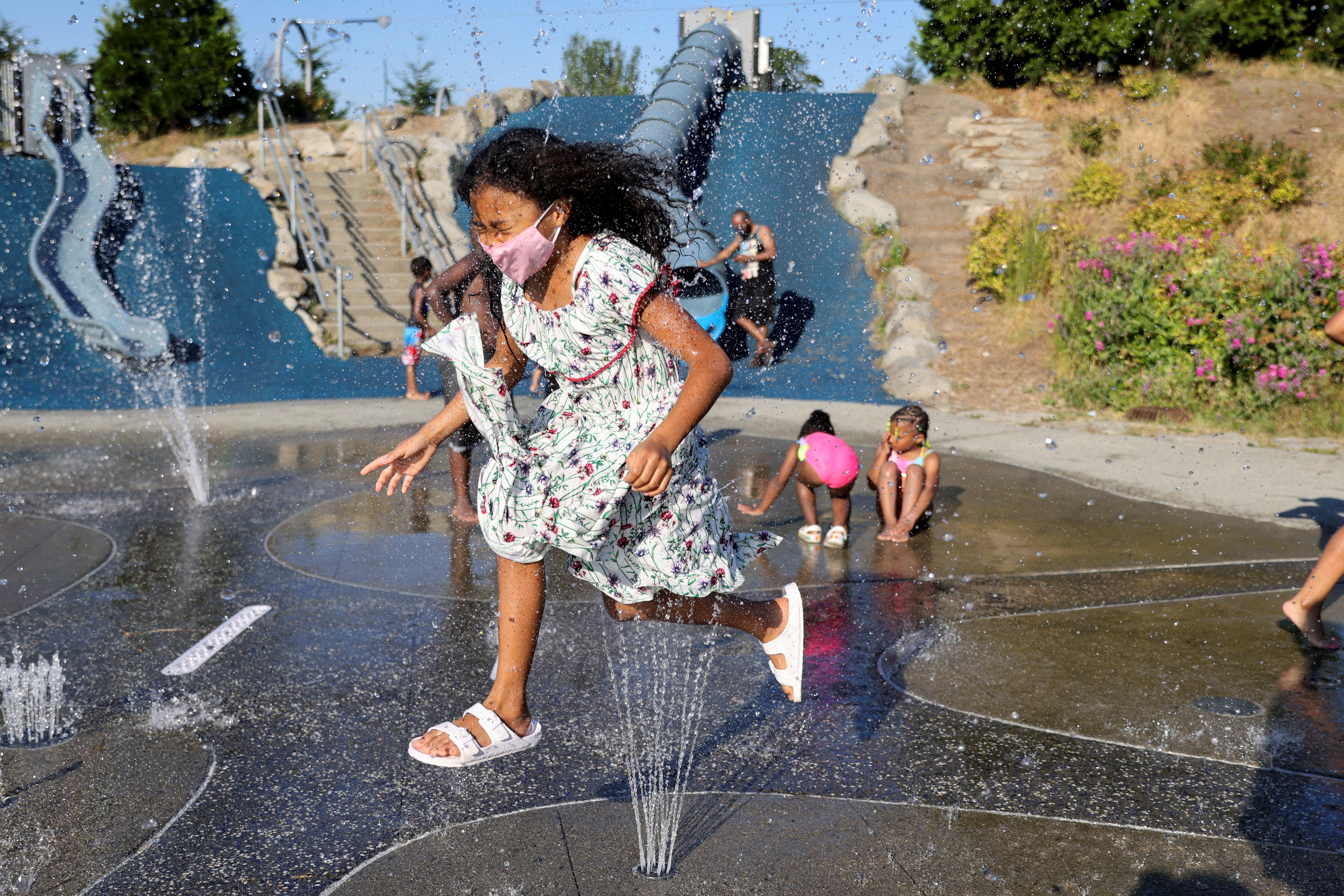 Isis Macadaeg, age 7, plays in a spray park at Jefferson Park during a heat wave in Seattle, Washington, U.S., June 27, 2021. REUTERS/Karen Ducey