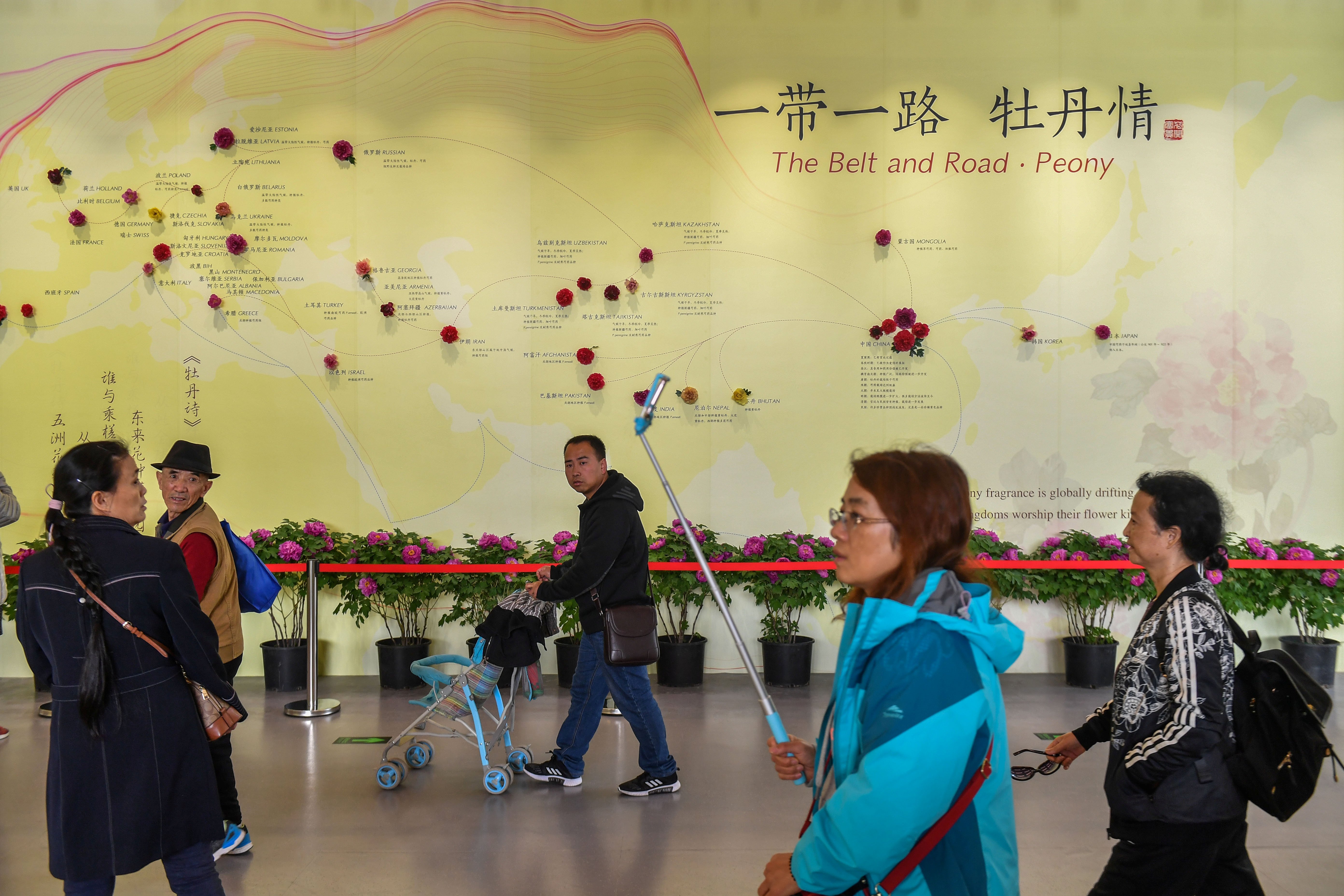 Visitors walk past a wall with a map showing the species of peony in Belt and Road Initiative (BRI) countries, at horticultural exhibition Beijing Expo 2019, in Beijing, China April 29, 2019. Picture taken April 29, 2019. REUTERS/Stringer