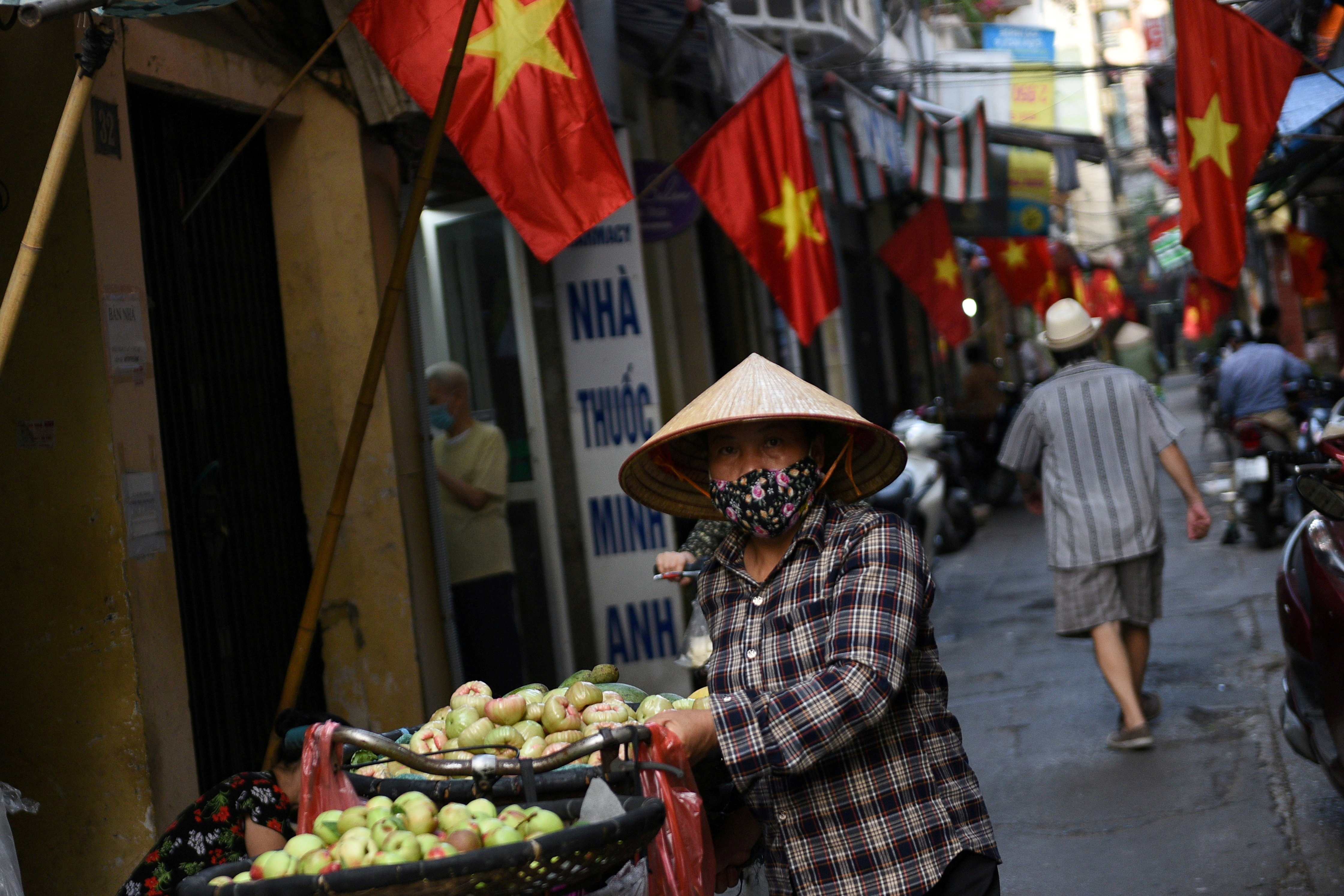 A vendor walks in an alley decorated with national flags ahead of the upcoming elections in Hanoi, Vietnam, May 19, 2021. Picture taken May 19, 2021.  REUTERS/Thanh Hue/File Photo
