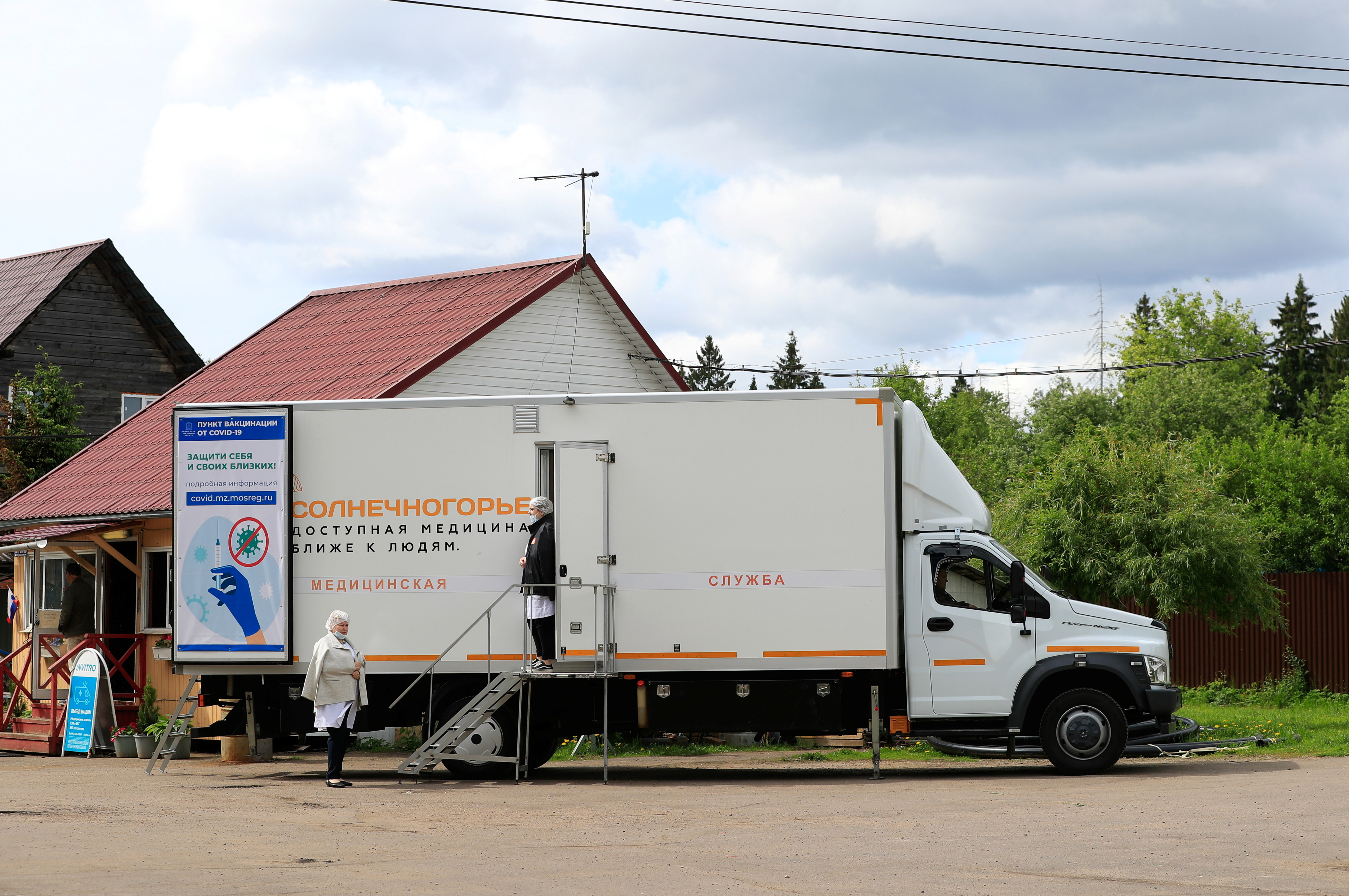 Medical workers are seen at a mobile coronavirus disease (COVID-19) vaccination centre in a dacha community near the village of Poyarkovo in Moscow Region, Russia May 31, 2021.  REUTERS/Evgenia Novozhenina/File Photo