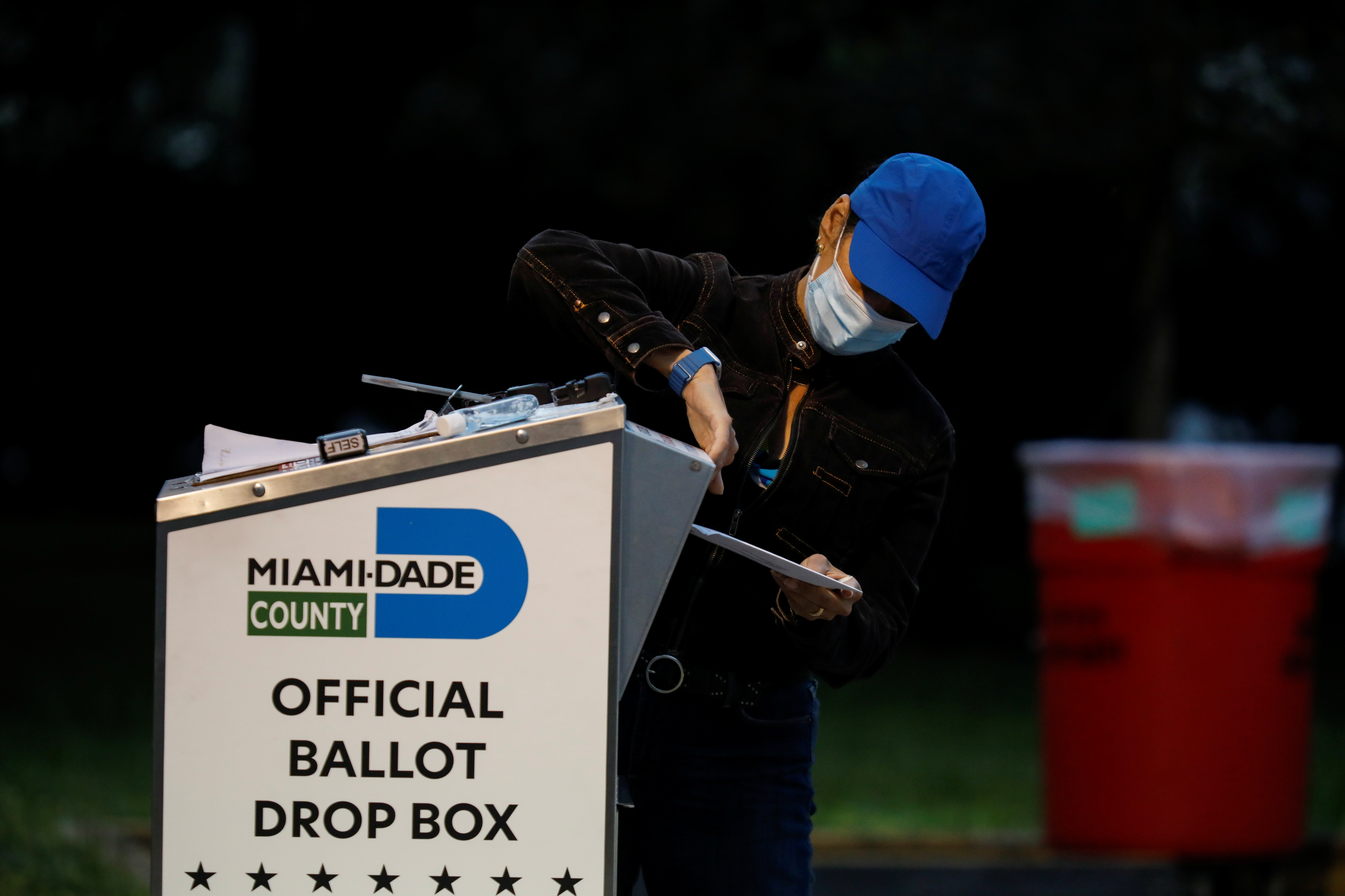 A poll worker casts a mail-in ballot for a voter at a drive-thru polling station at Miami-Dade County Elections Department during the 2020 presidential election in Miami, Florida, U.S., November 3, 2020. REUTERS/Marco Bello - RC20WJ946HIN