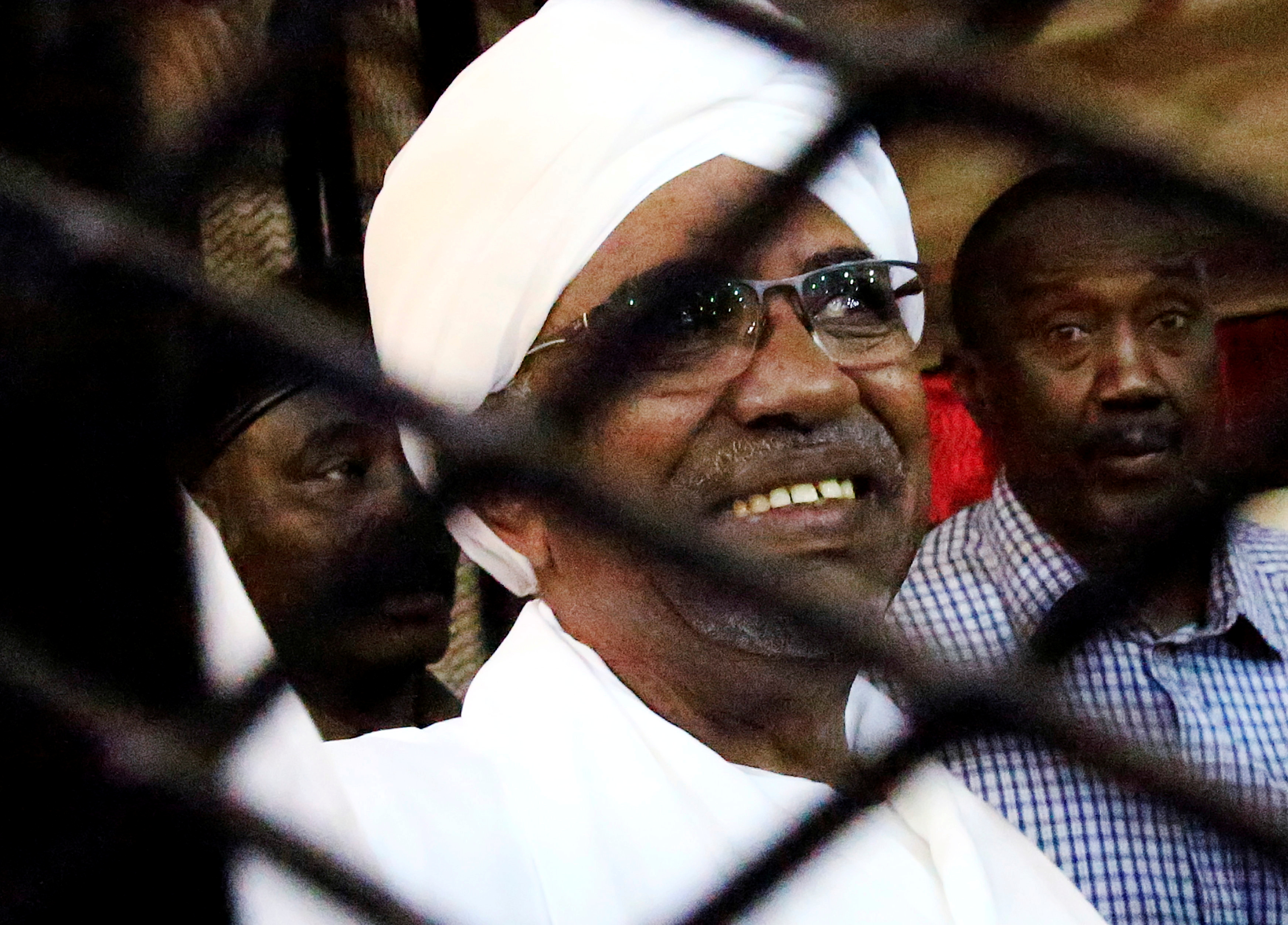 Sudan's former president Omar Hassan al-Bashir smiles as he is seen inside a cage at the courthouse where he is facing corruption charges, in Khartoum, Sudan August 31, 2019. REUTERS/Mohamed Nureldin Abdallah/File Photo