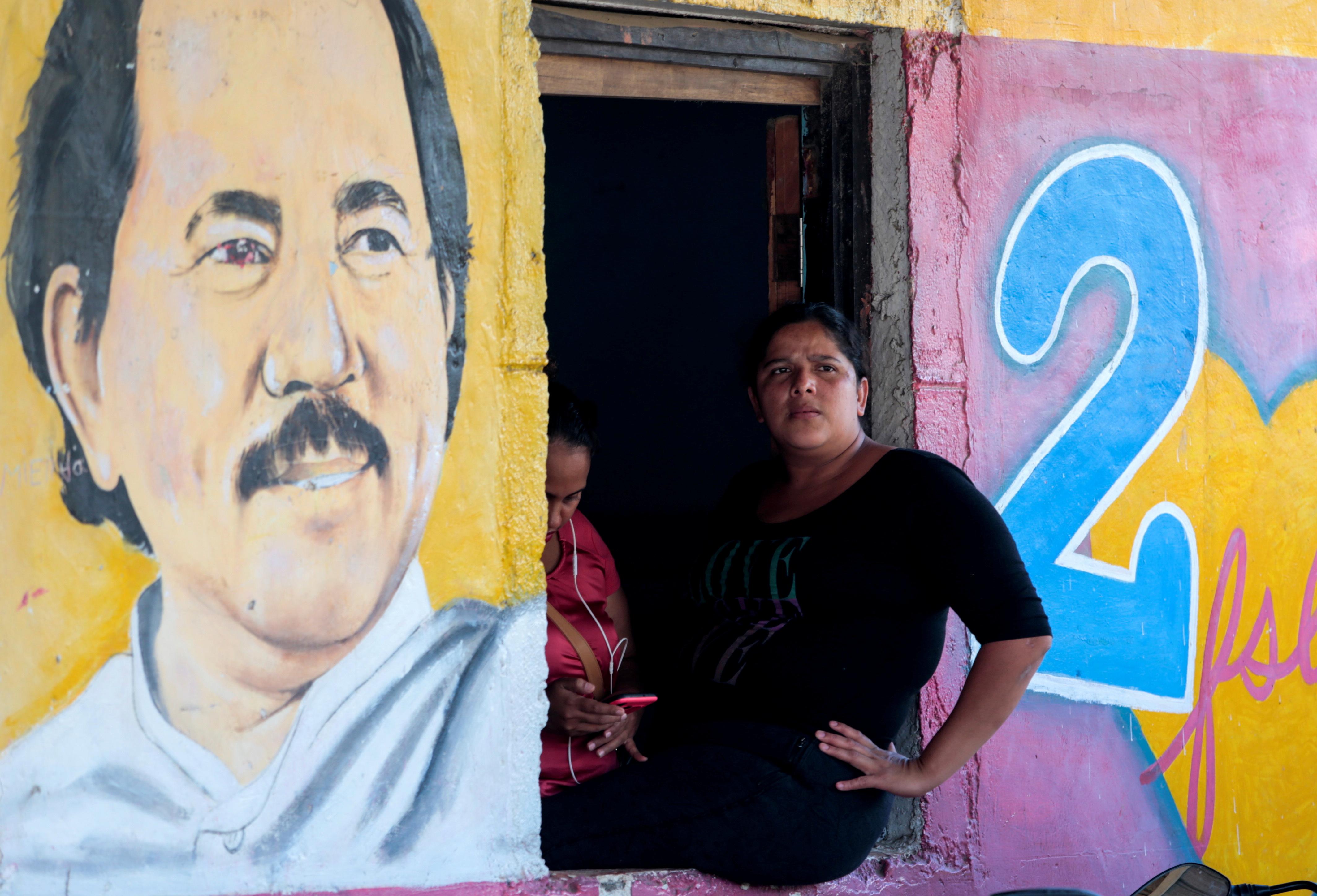 A woman sits next to an image of Nicaragua's President Daniel Ortega in Catarina, Nicaragua October 1, 2020.REUTERS/Oswaldo Rivas/File Photo
