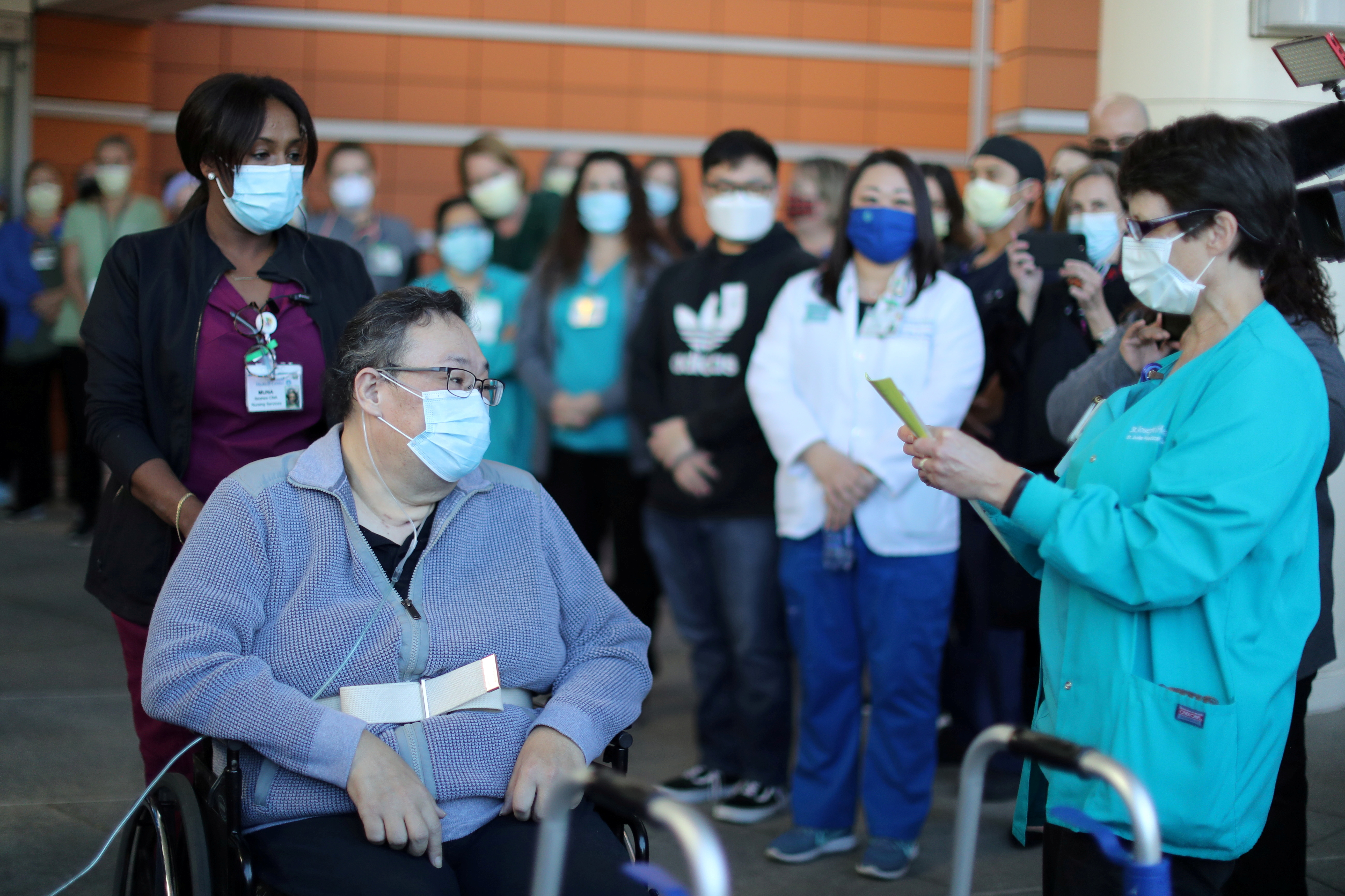 A medical worker reads a poem to Daniel Kim, 48, as he leaves St. Jude Medical Center after five months after surviving the coronavirus disease (COVID-19), in Fullerton, California, U.S., December 16, 2020. REUTERS/Lucy Nicholson