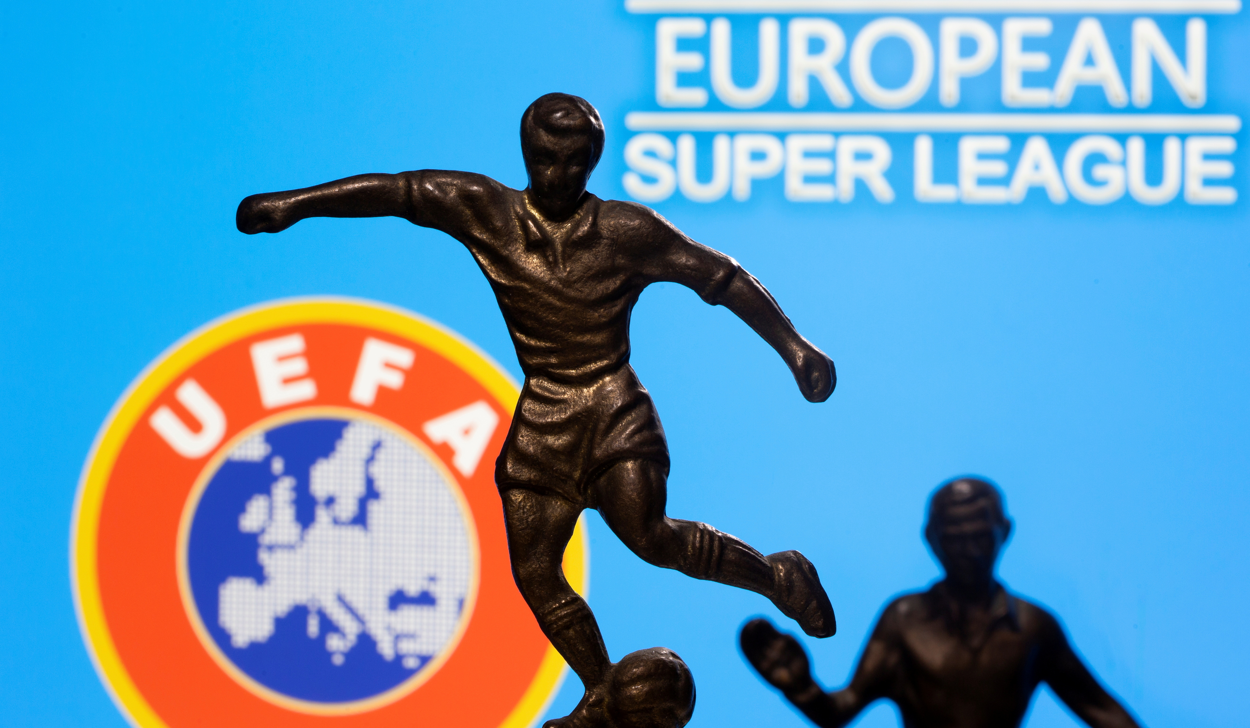 Metal figures of football players are seen in front of the words