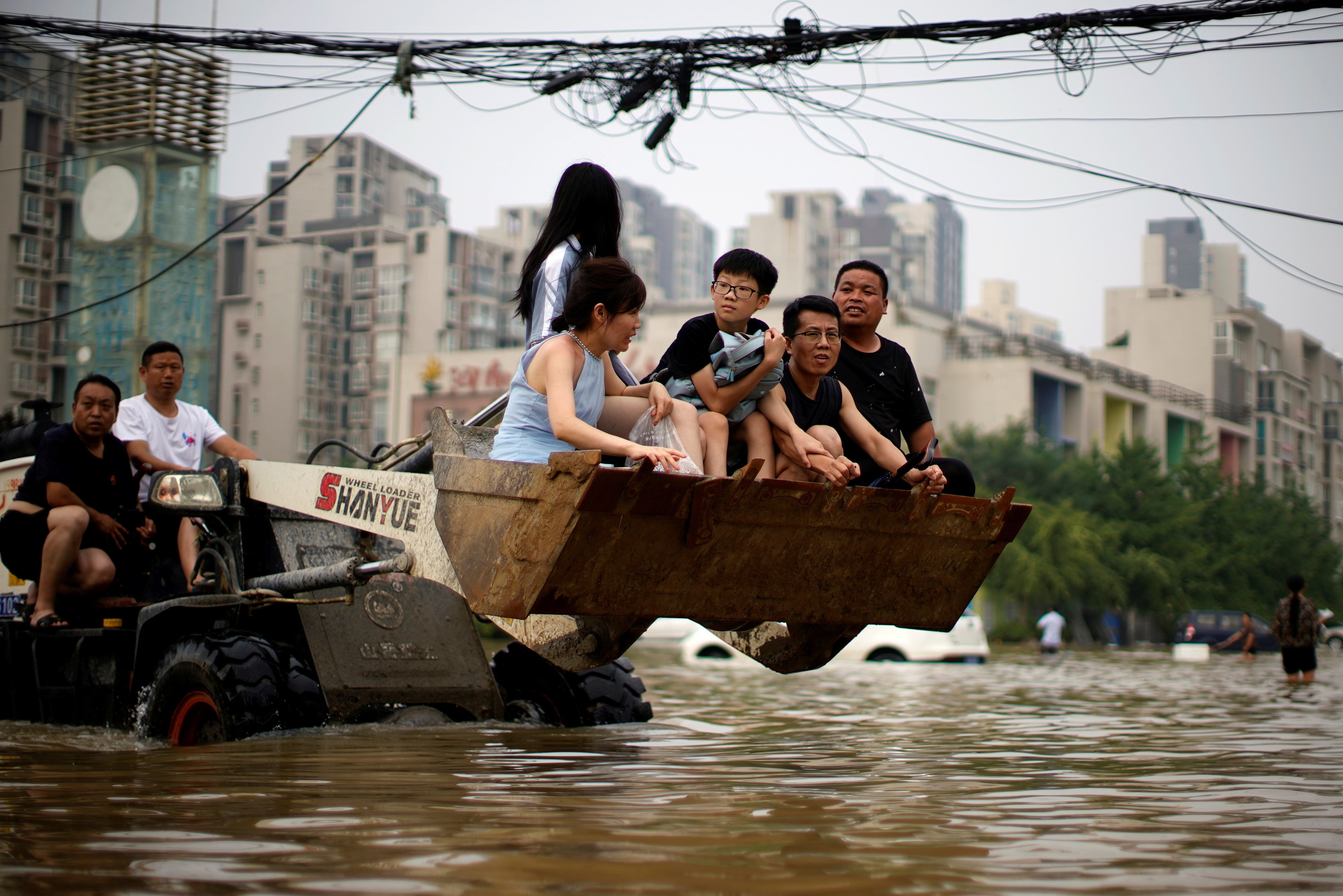 People ride on a front loader as they make their way through floodwaters following heavy rainfall in Zhengzhou, Henan province, China July 23, 2021. REUTERS/Aly Song/File Photo
