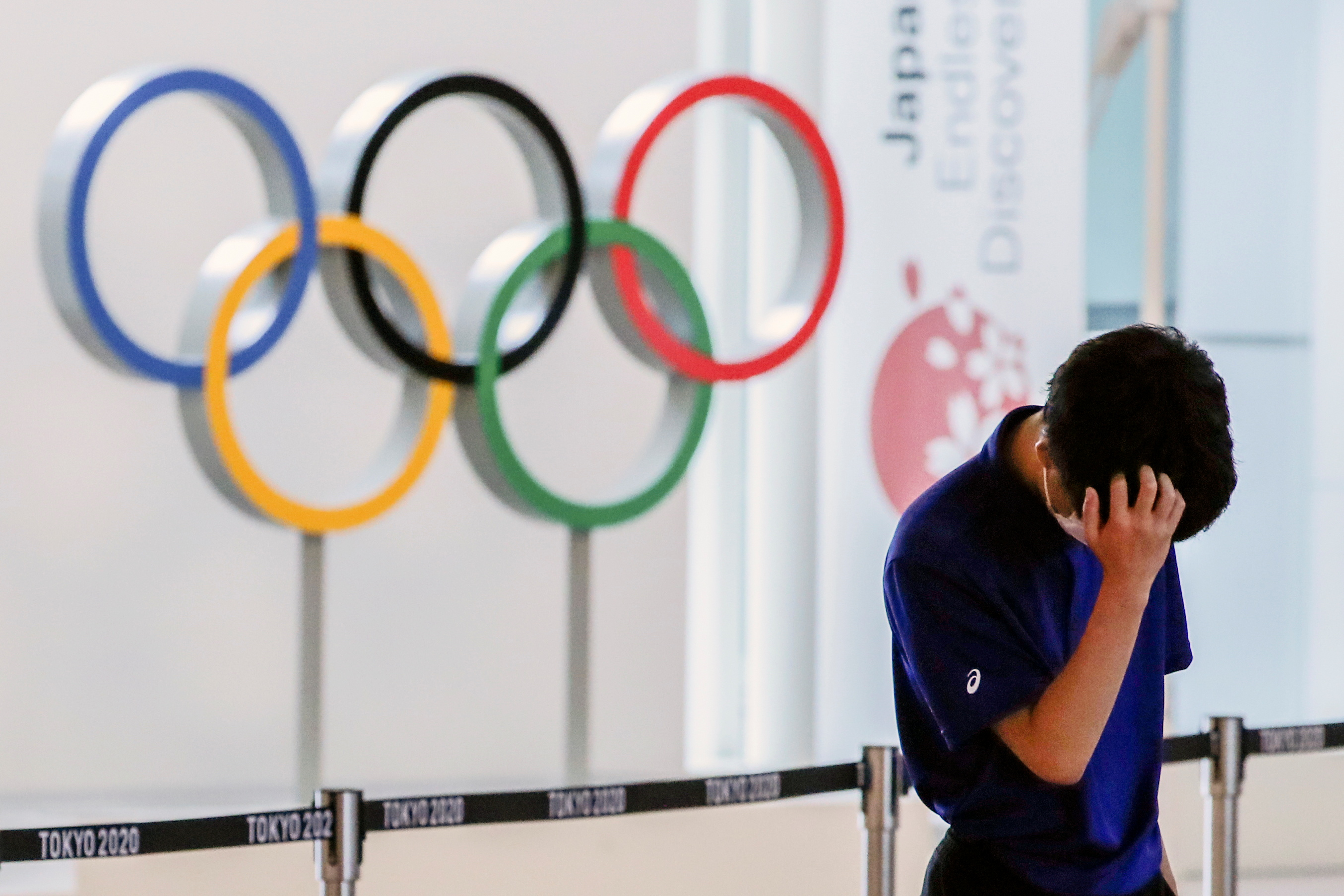 A staff standing in front of Olympic rings reacts while waiting for the arrival of foreign athletes at Haneda Airport ahead of Tokyo 2020 Olympic Games, in Tokyo, Japan July 8, 2021. REUTERS/Kim Kyung-Hoon