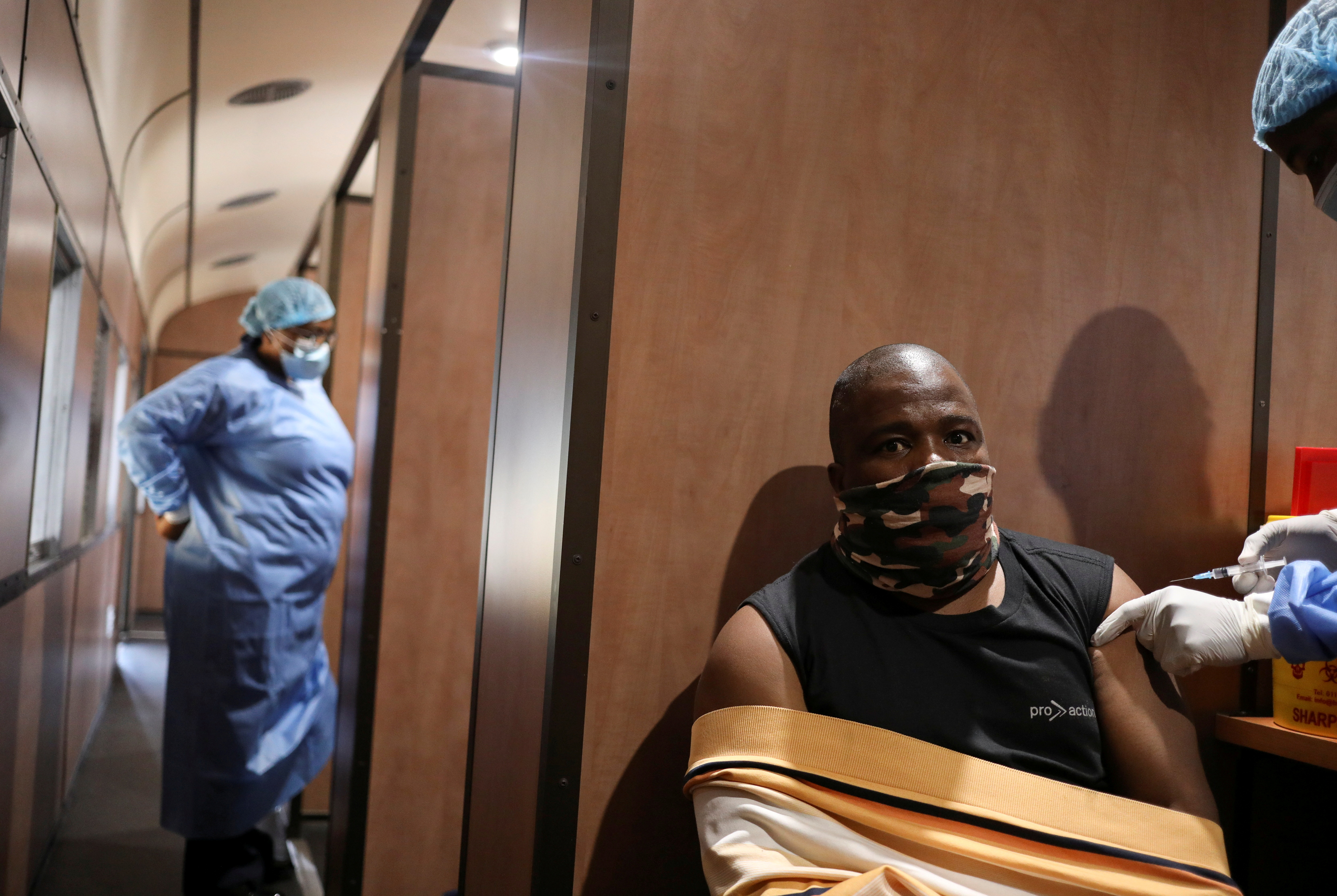 Dennis Malattji takes his coronavirus vaccine while a health worker looks on inside the Transvaco COVID-19 vaccine train, at the Springs train station on the East Rand, South Africa, August 27, 2021. REUTERS/Siphiwe Sibeko/File Photo