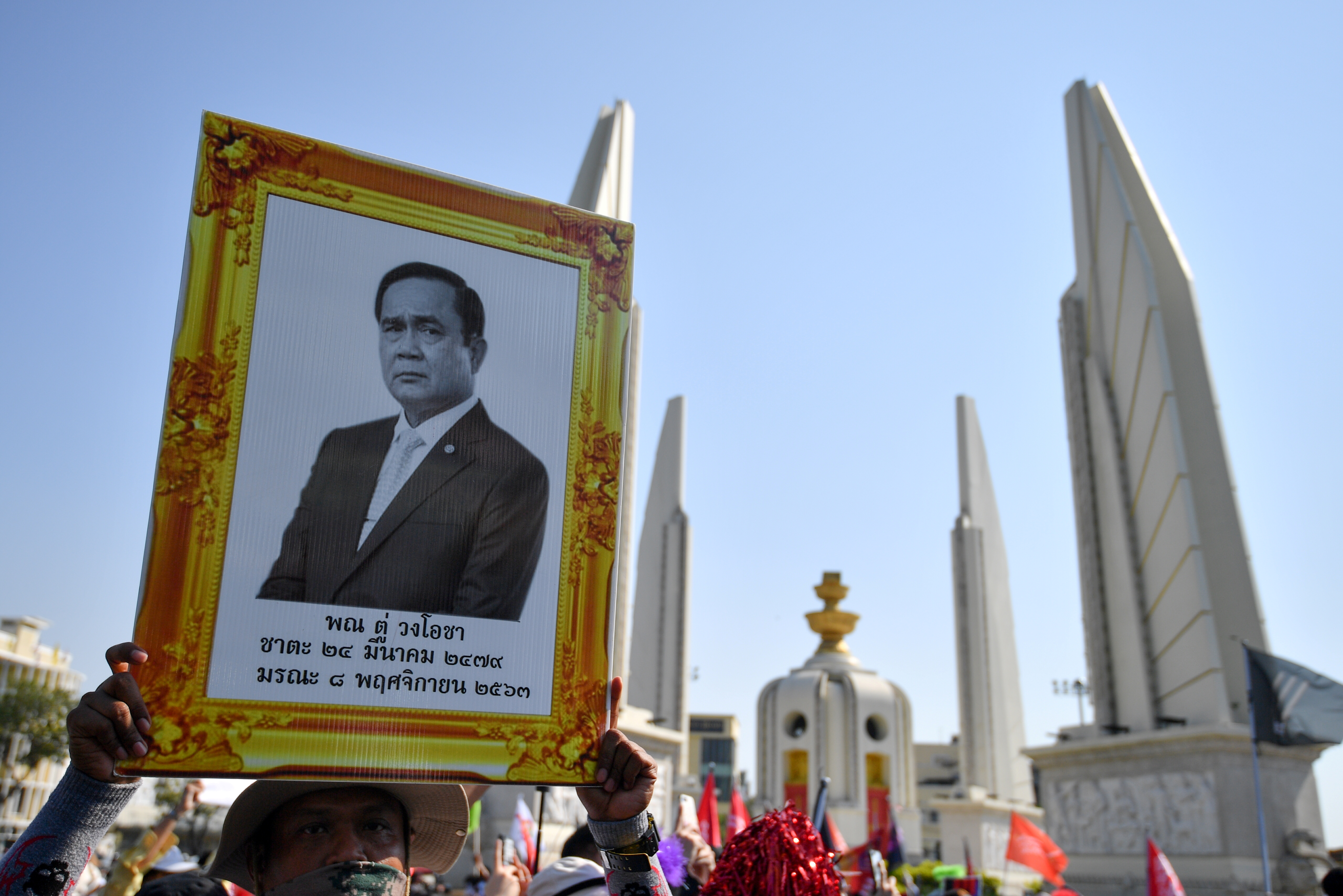 A pro-democracy demonstrator holds a portrait of Thai Prime Minister Prayuth Chan-ocha, at at gathering at Democracy Monument to demand the release of four protestors who were charged under a lese majeste law, in Bangkok, Thailand, March 7, 2021. REUTERS/Chalinee Thirasupa/File Photo
