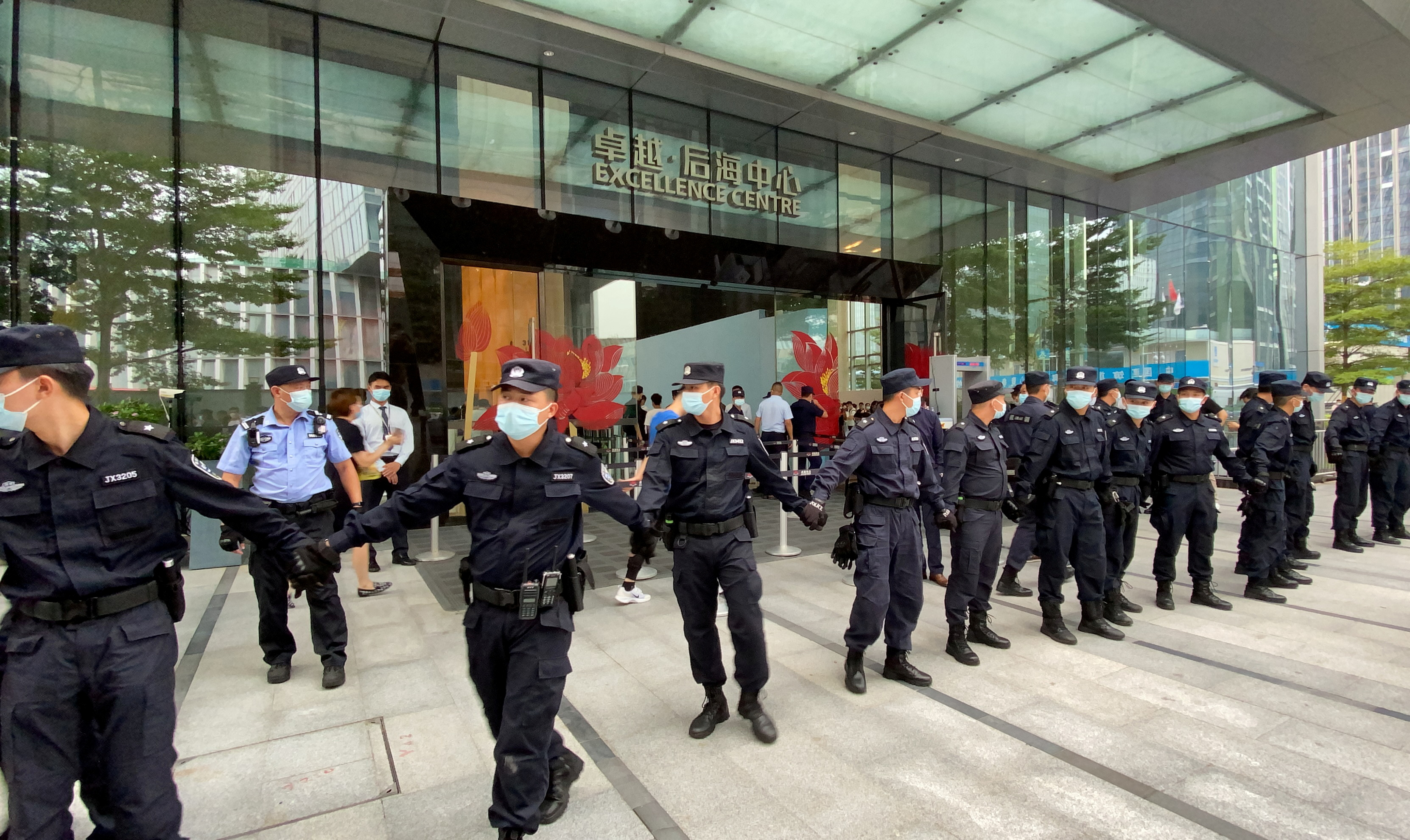 Security personnel form a human chain as they guard outside the Evergrande's headquarters, where people gathered to demand repayment of loans and financial products, in Shenzhen, Guangdong province, China September 13, 2021. REUTERS/David Kirton/File Photo