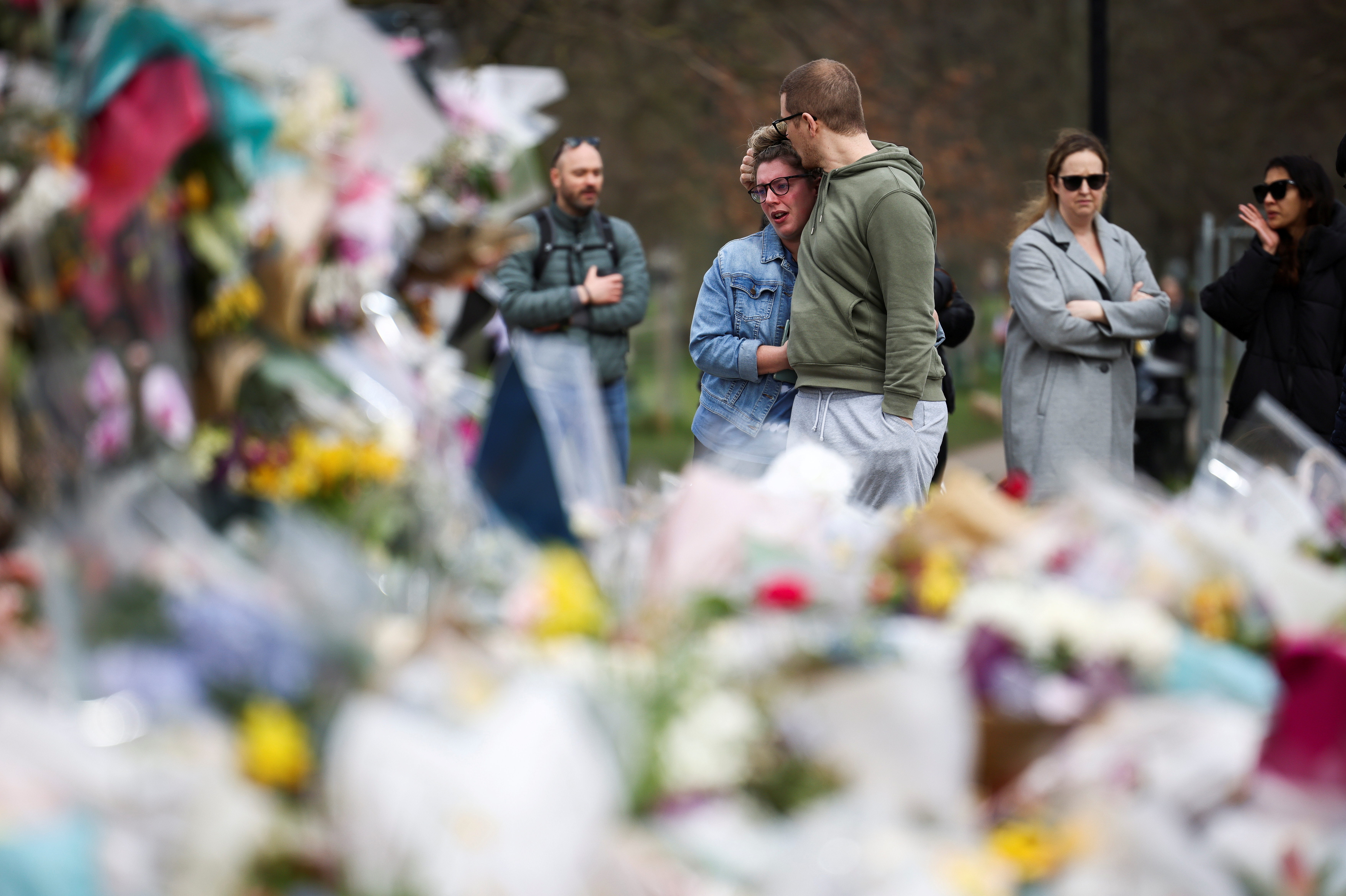 People observe a memorial site at the Clapham Common Bandstand, following the kidnapping and murder of Sarah Everard, in London, Britain, March 21, 2021. REUTERS/Henry Nicholls/File Photo