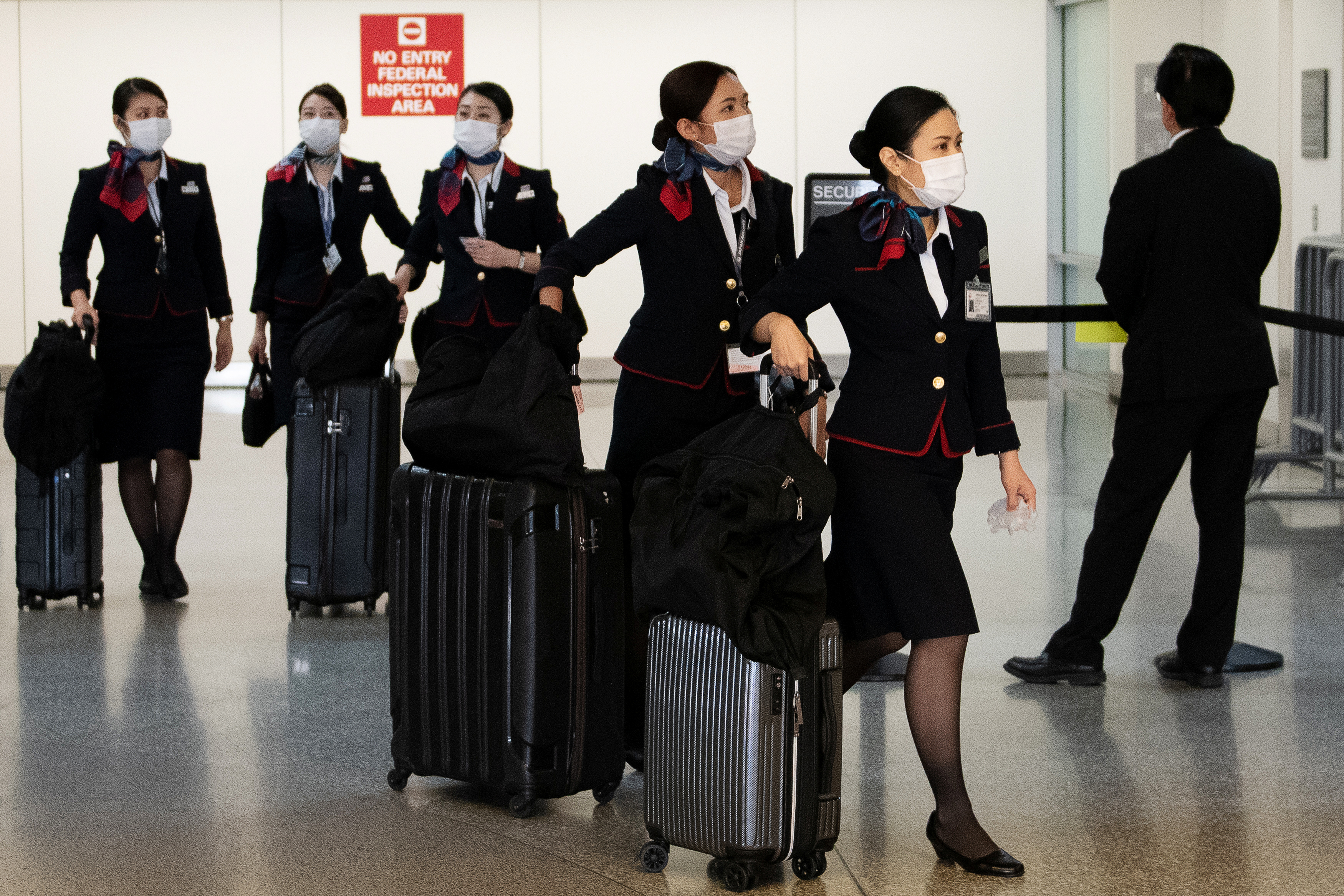 Japan Airlines flight attendants arrive at San Francisco International Airport wearing protective face masks in San Francisco, California, U.S. March 13, 2020.REUTERS/Kate Munsch