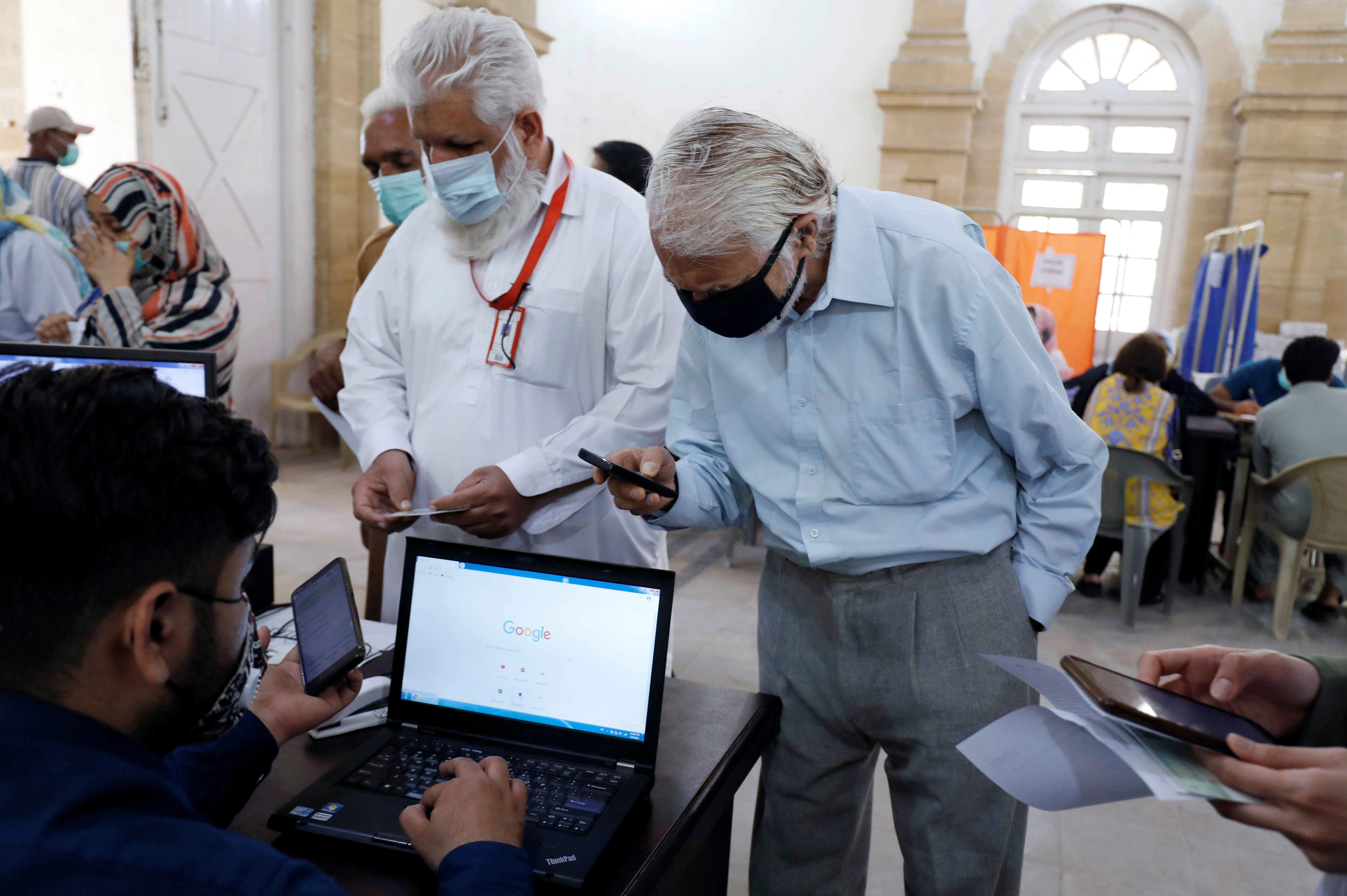 Residents check-in for their dose of the coronavirus disease (COVID-19) vaccine, as the government started vaccination for the general public, starting with elderly people, at a vaccination center in Karachi, Pakistan March 10, 2021. REUTERS/Akhtar Soomro