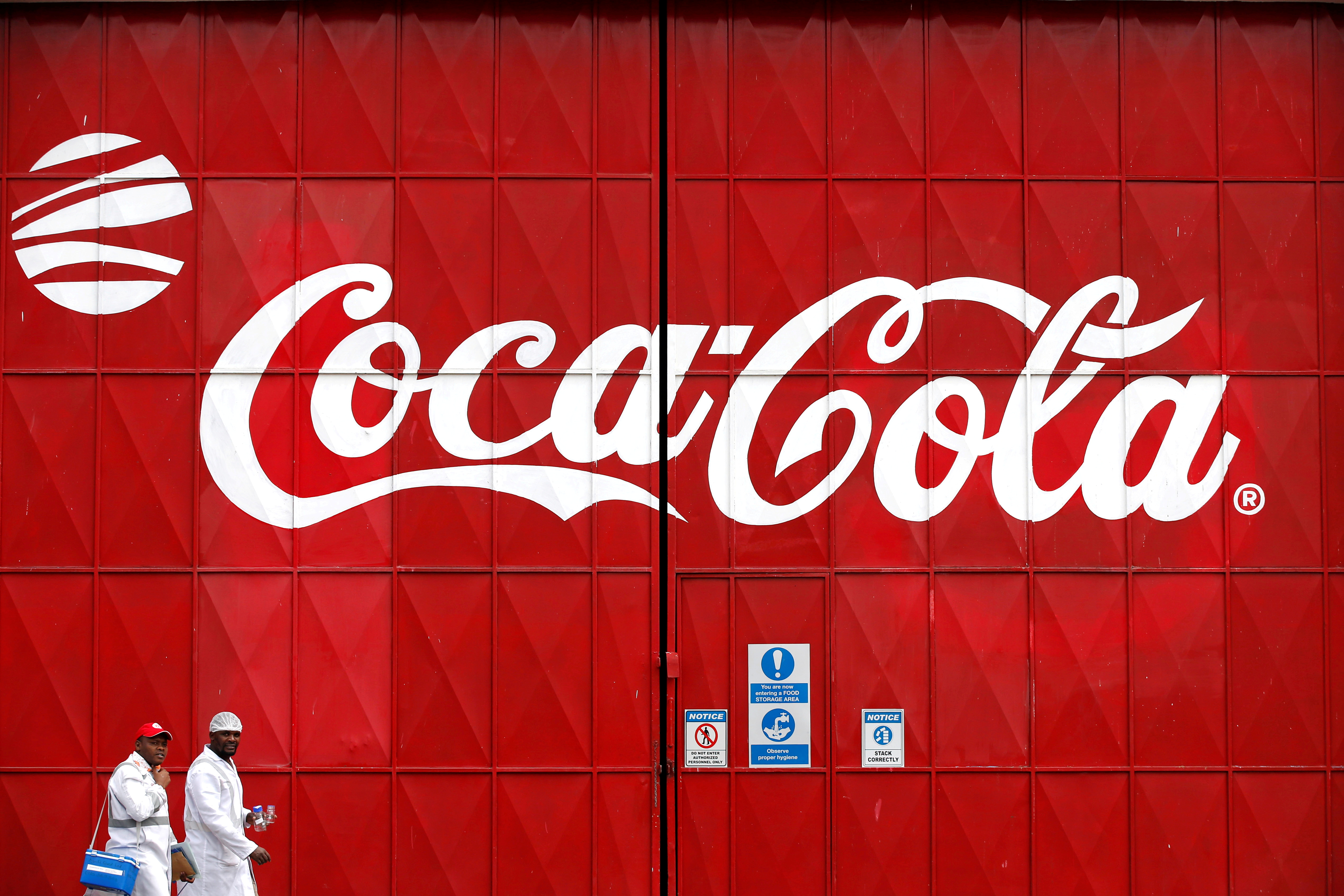 Workers walk past a Coca Cola logo painted on a gate at a Coca Cola factory in Nairobi, Kenya, June 7, 2018. REUTERS/Baz Ratner/File Photo