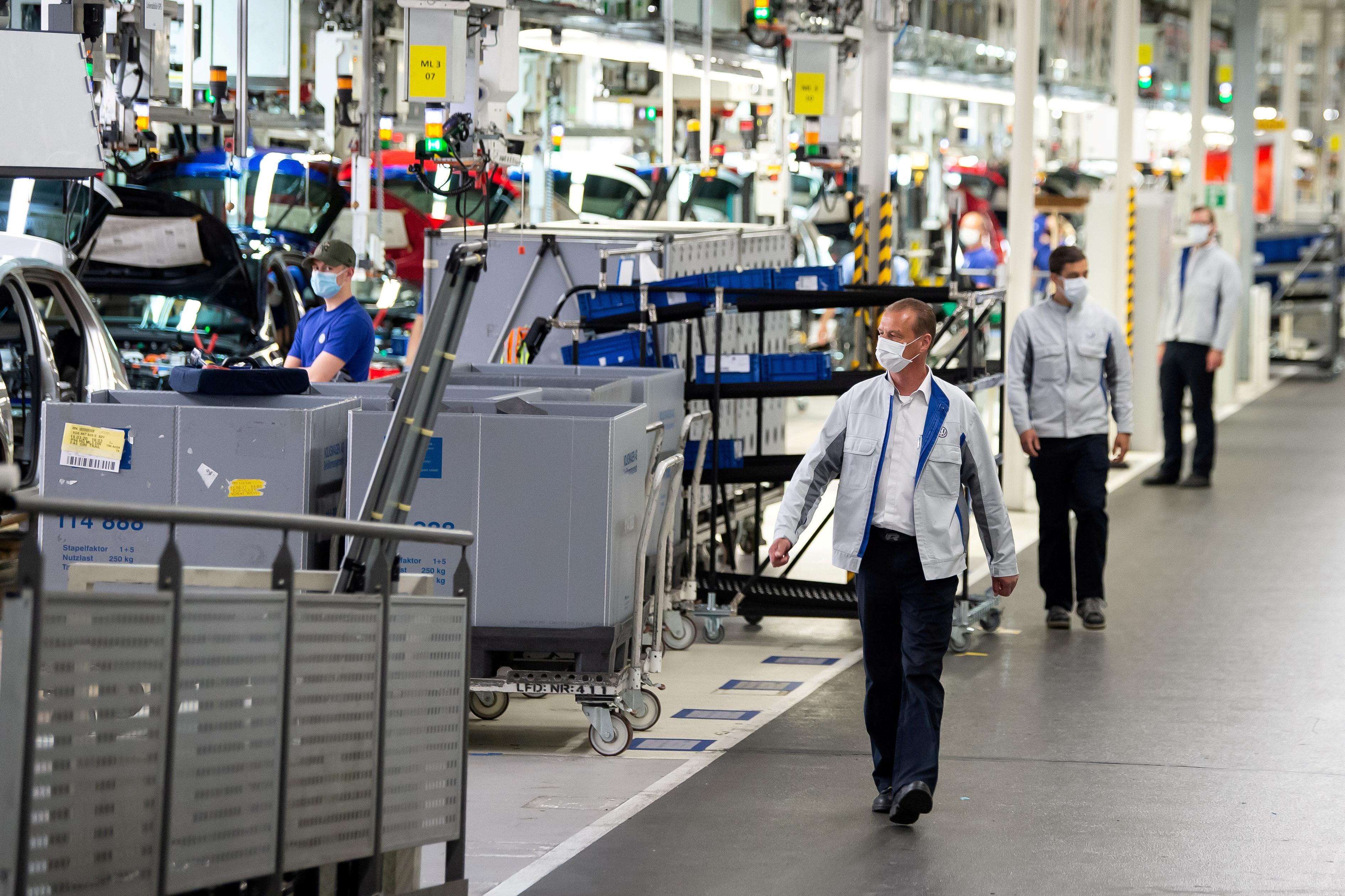 El personal usa máscaras protectoras en la línea de ensamblaje de Volkswagen en Wolfsburg, Alemania, el 27 de abril de 2020. Swen Pfoertner / Pool vía REUTERS