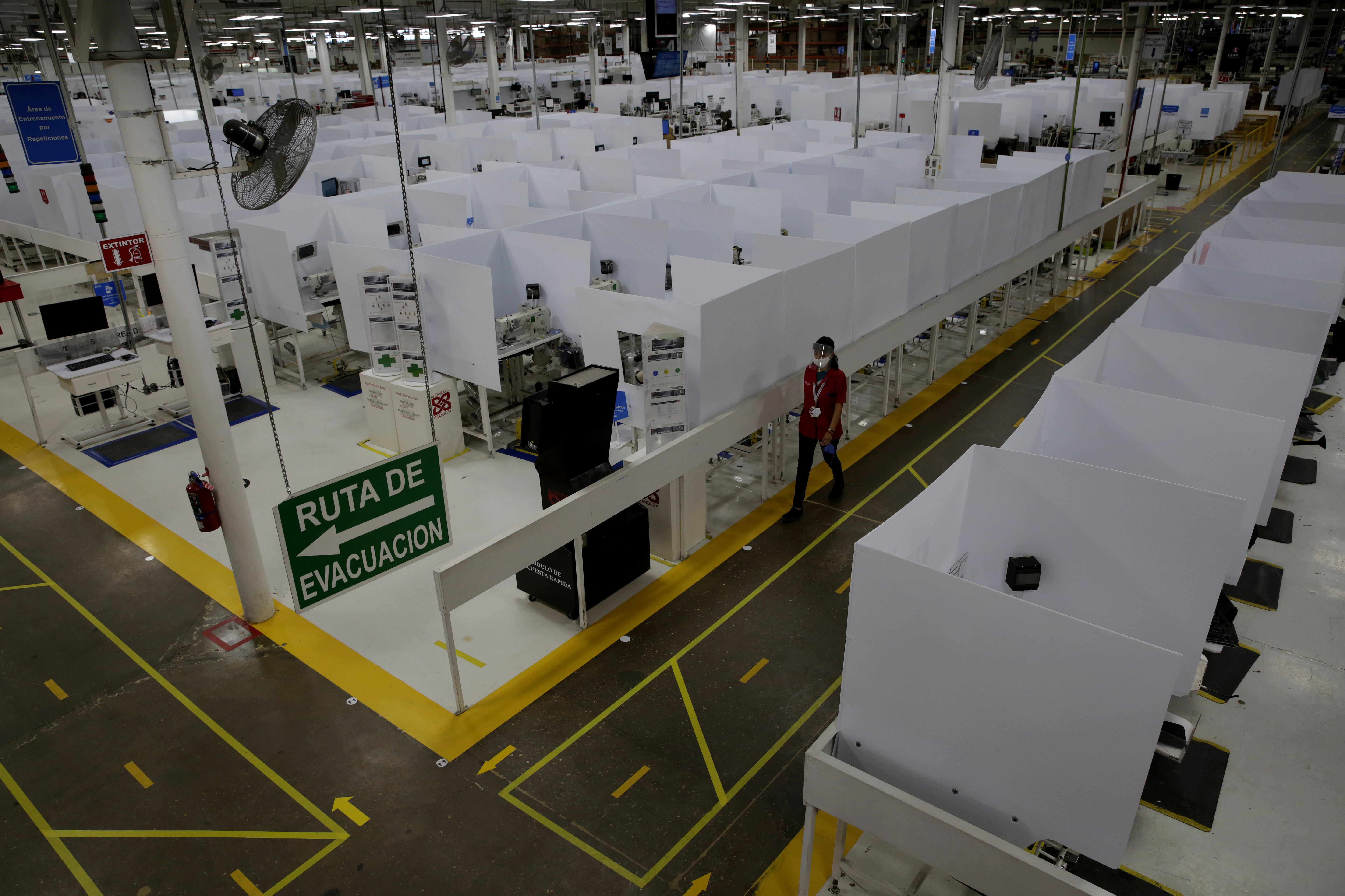 An employee of U.S. auto part maker Lear Corp., wearing a protective face mask, walks past work cubicles furnished with tall dividers as part of the new security measures at the plant, before resuming operations during the coronavirus disease (COVID-19) outbreak, in Ciudad Juarez, Mexico, May 27, 2020. REUTERS/Jose Luis Gonzalez