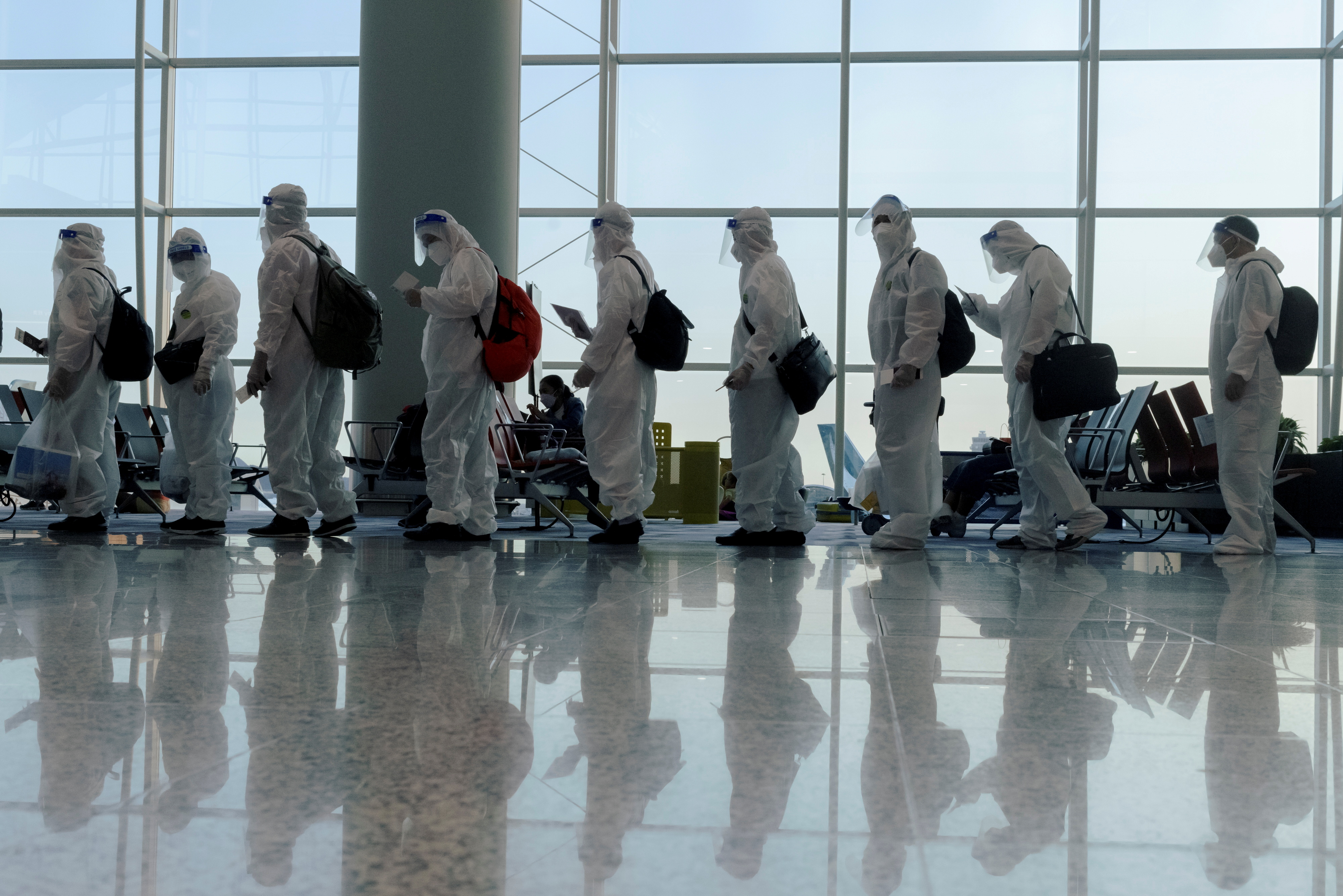Passengers wearing protective suits (PPE) line up to board their plane for an international flight at Hong Kong airport amid the spread of the coronavirus disease (COVID-19), China July 9, 2021. REUTERS/Thomas Peter/File Photo