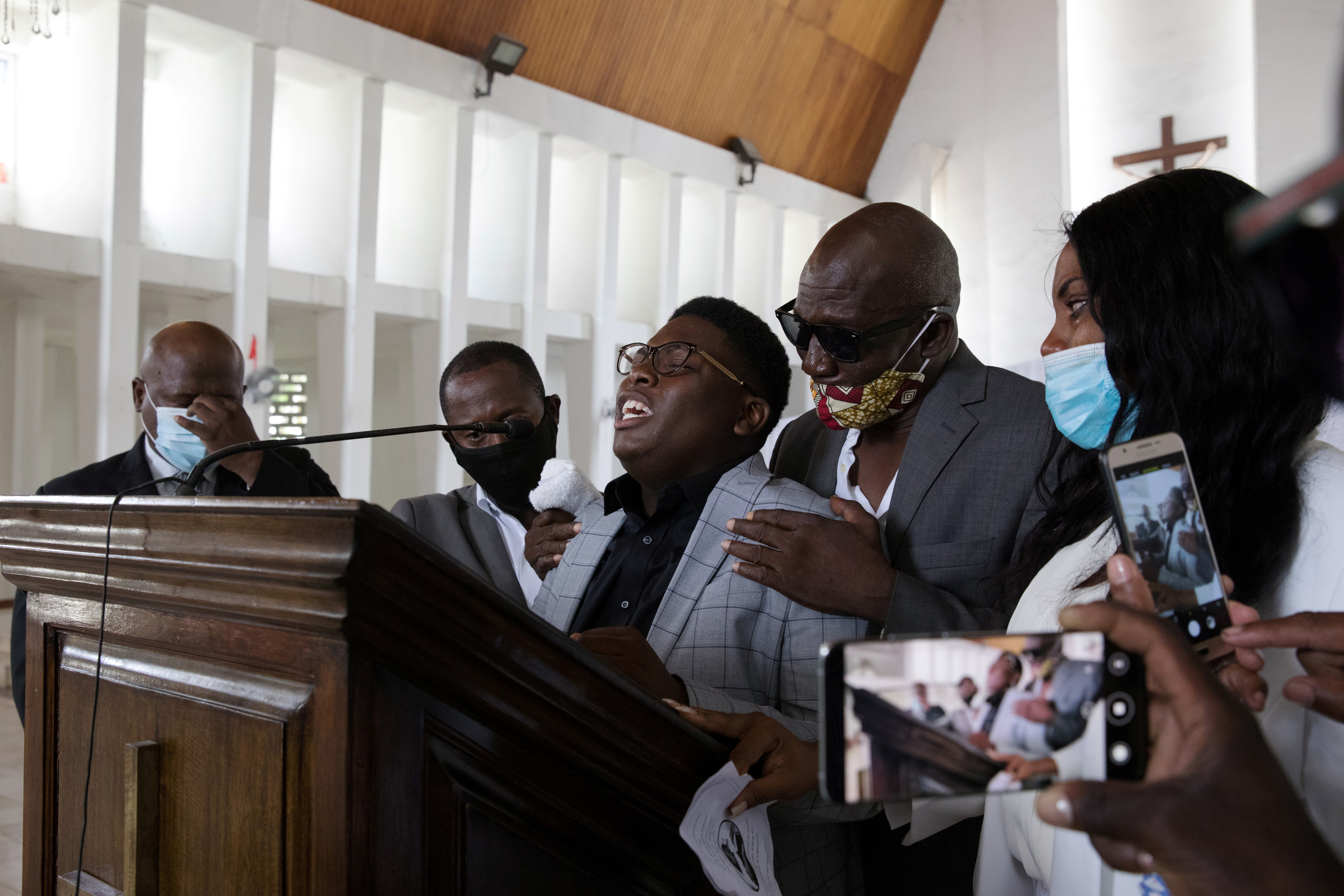 Anderson Laroche, 17, makes an emotional farewell speech to his deceased mother, Germanie Pierre in front of his family in Gonaives, Haiti, June 12, 2021. Despite the country's poverty, funerals are often extravagant social events in Haiti, complete with a festive wake and fanfare bands. Haiti's death rites are viewed as important to guarantee a safe passage to the afterworld – with cremations and organ donations rare because the deceased are deemed still to need their bodies - but also a way to mark one's social standing. REUTERS/Valerie Baeriswyl