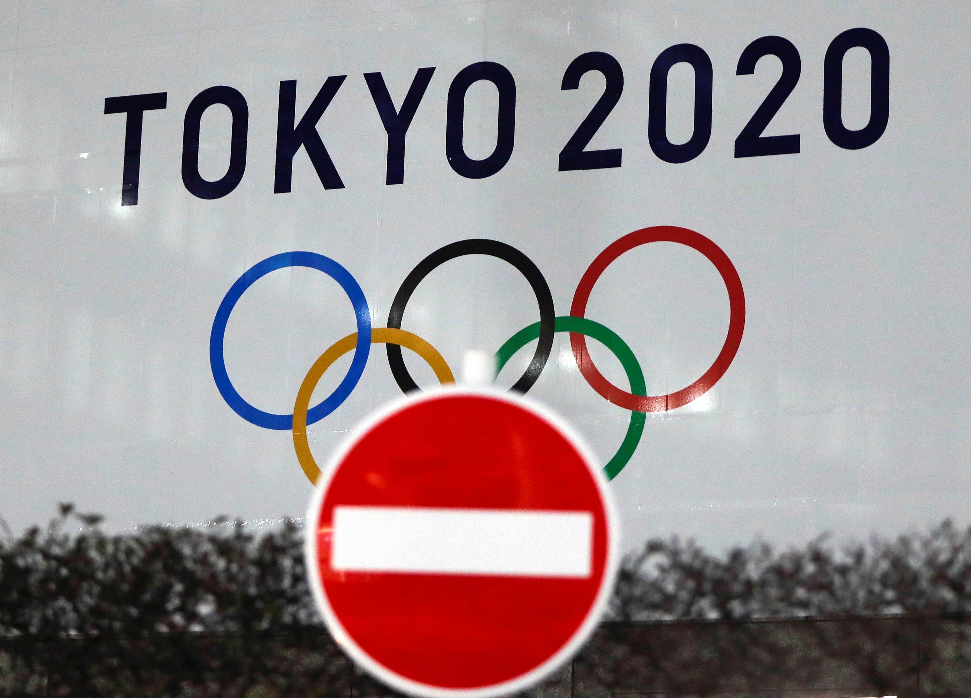 Biểu trưng của Thế vận hội Olympic Tokyo 2020 đã bị hoãn đến năm 2021 do dịch bệnh coronavirus (COVID-19) bùng phát, được nhìn thấy qua một biển báo giao thông tại tòa nhà Văn phòng Chính phủ Thủ đô Tokyo ở Tokyo, Nhật Bản ngày 22 tháng 1 năm 2021. REUTERS / Issei Kato