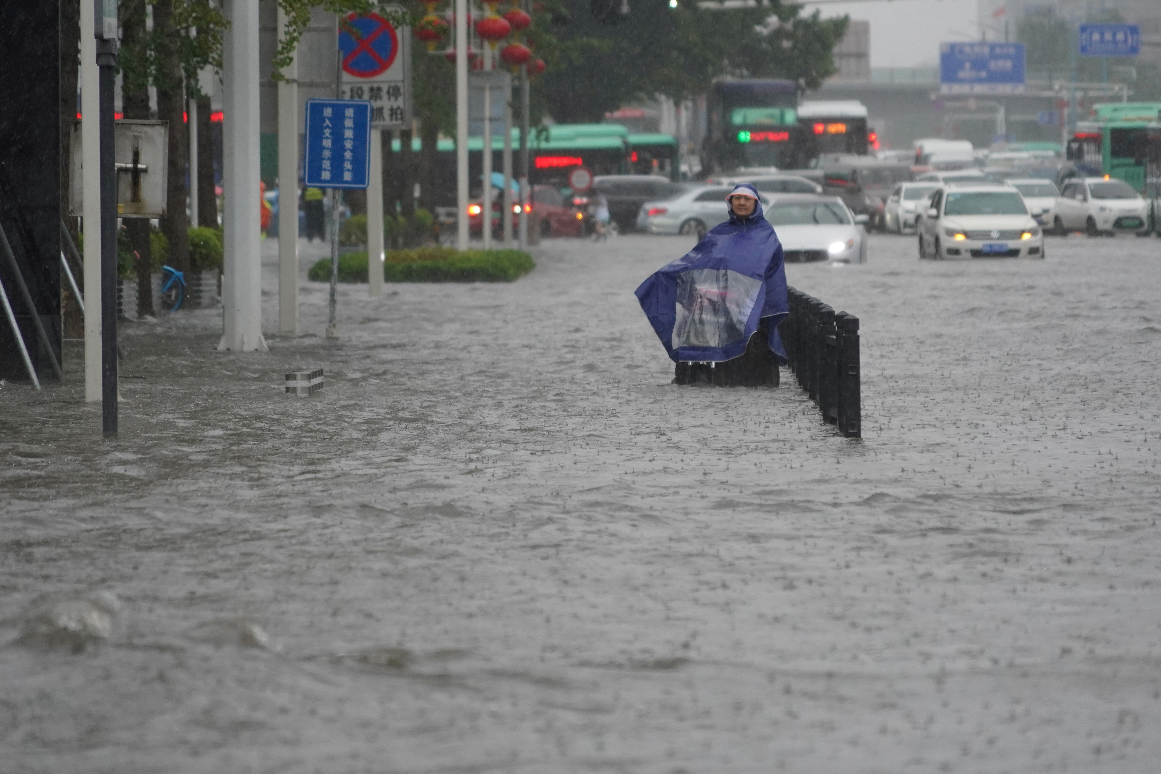 A resident wearing a rain cover stands on a flooded road in Zhengzhou, Henan province, China July 20, 2021. cnsphoto via REUTERS   ATTENTION EDITORS - THIS IMAGE WAS PROVIDED BY A THIRD PARTY. CHINA OUT.