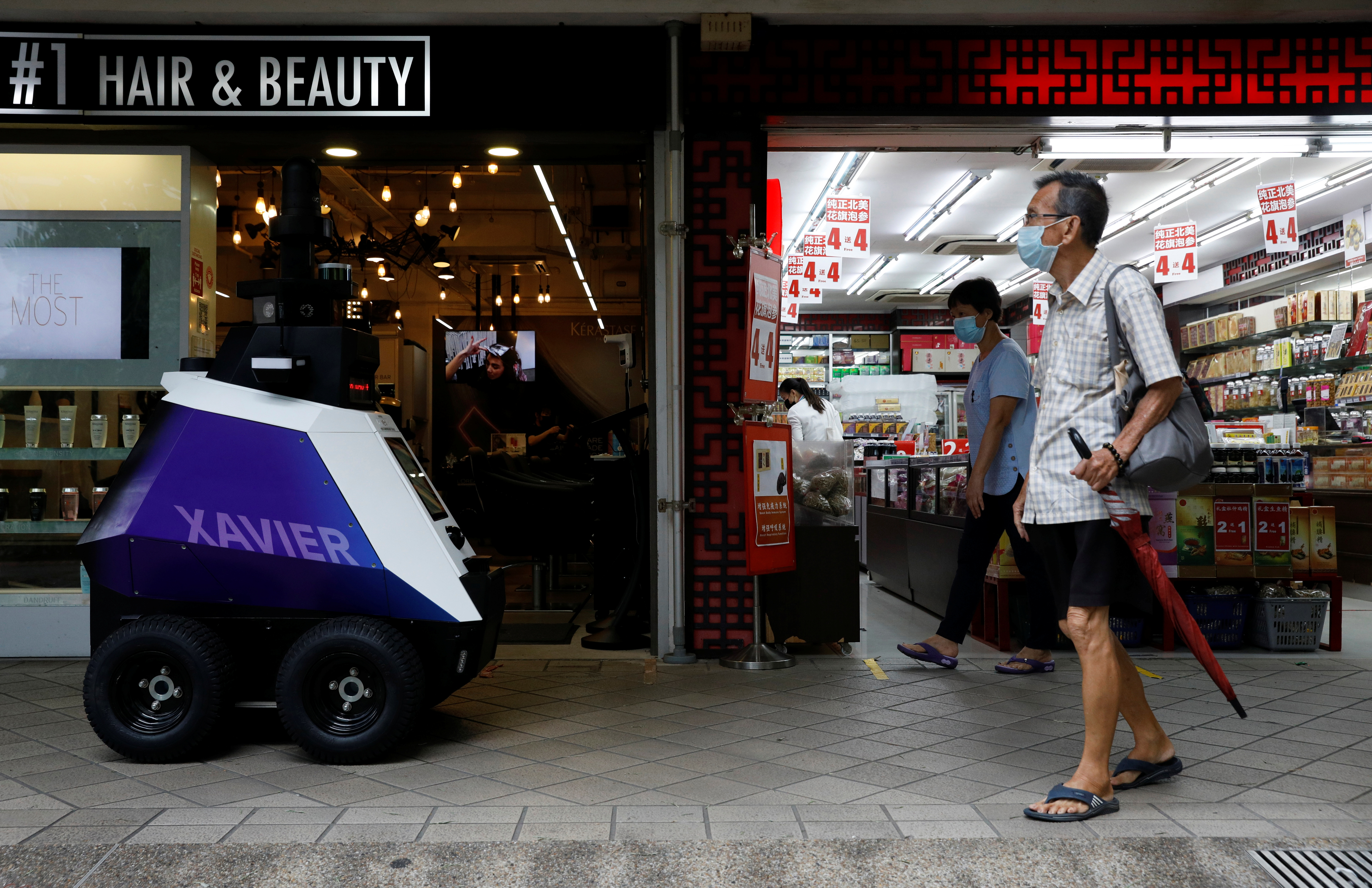 """Autonomous robot Xavier patrols a neighbourhood mall to detect """"undesirable social behaviours"""", such as the flouting of COVID-19 safety measures, smoking in prohibited areas and improperly parked bicycles, during a three-week trial in Singapore September 6, 2021. REUTERS/Edgar Su"""