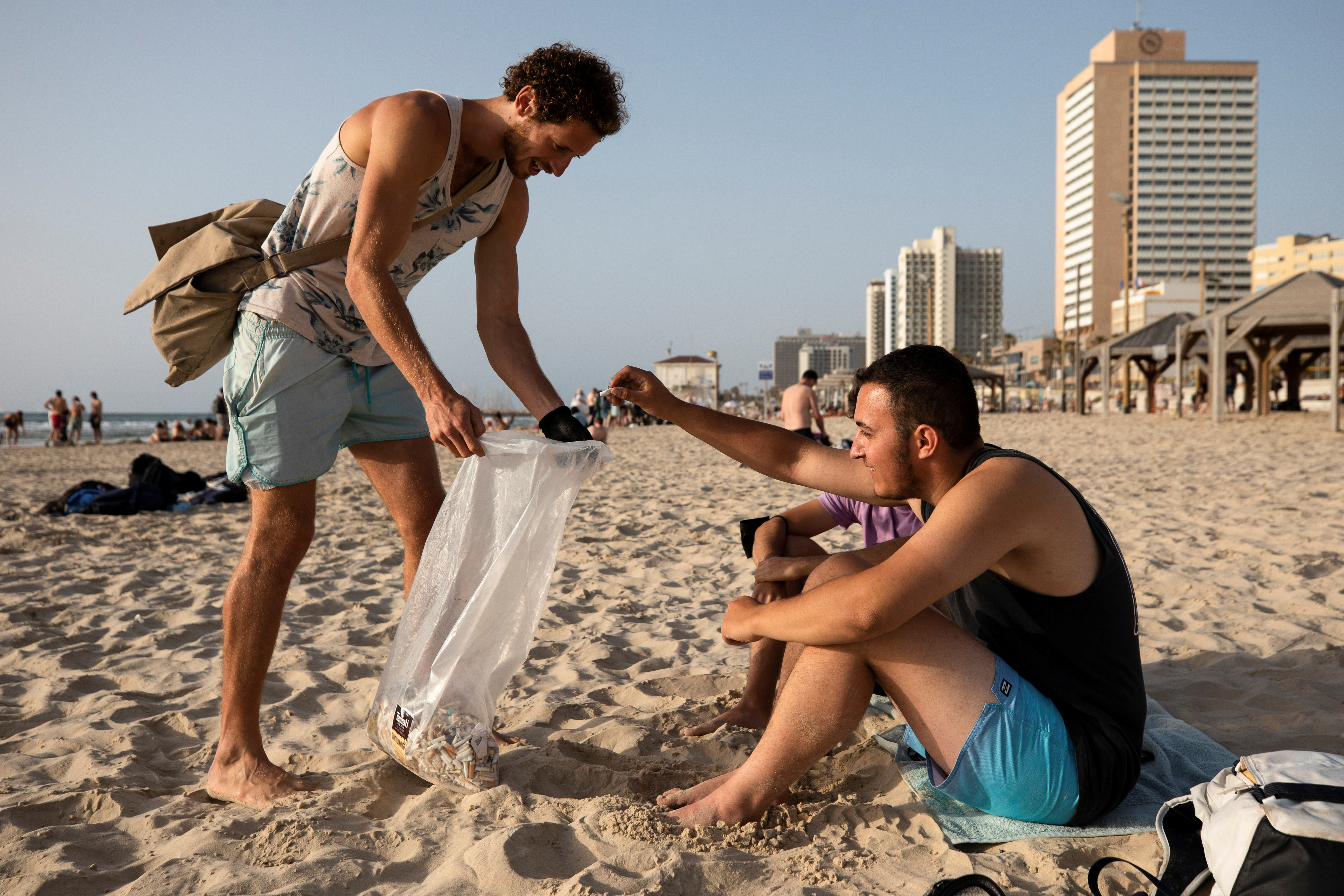 Julian Melcer collects a cigarette butt from a beach-goer as part of his environmental campaign at a beach in Tel Aviv, Israel April 20, 2021.   REUTERS/Amir Cohen