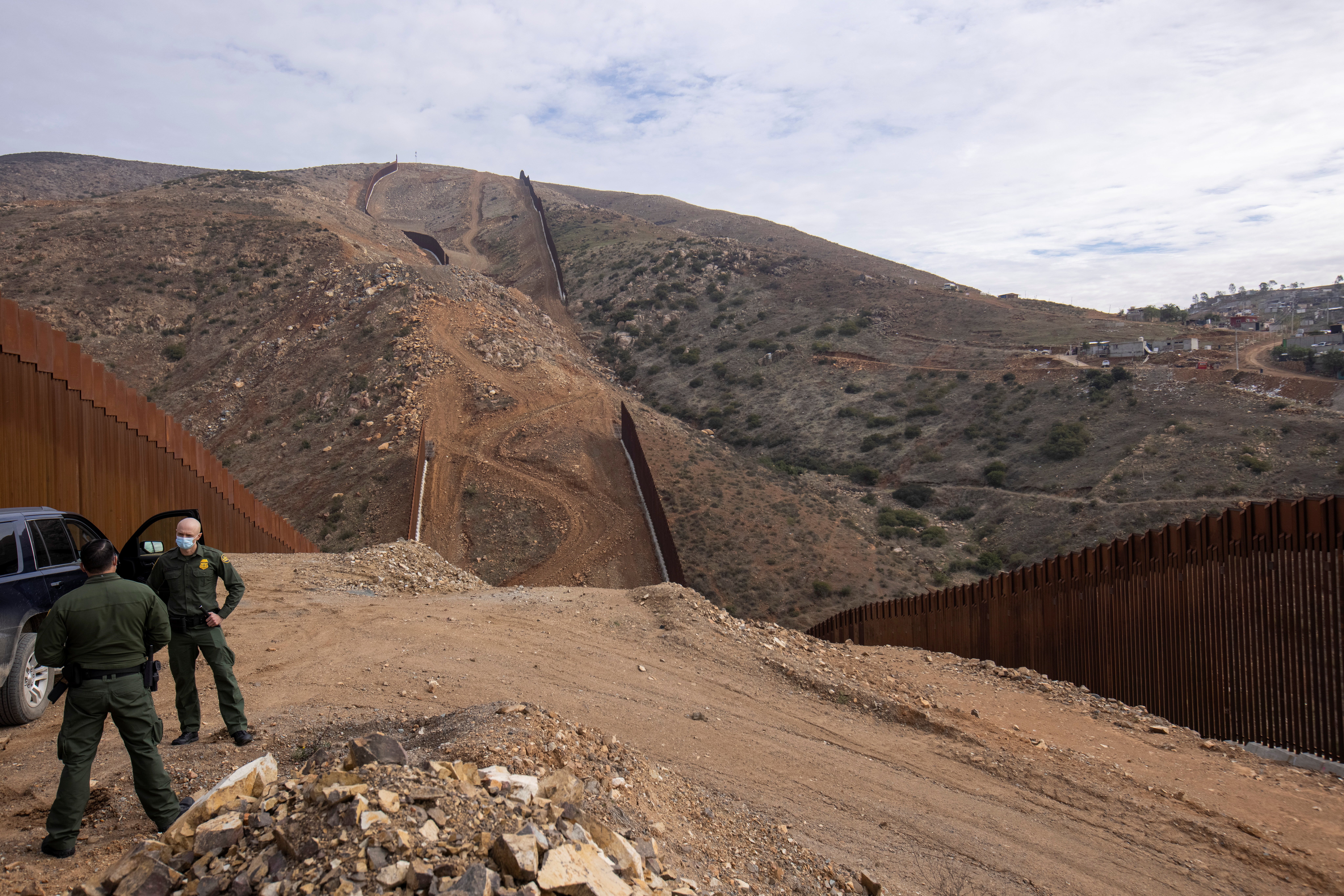 U.S. border patrol agents stand near the location of halted construction along the U.S. Border wall with Mexico as an unfinished  section is shown on Otay Mountain, east of San Diego, California, U.S., February 2, 2021. REUTERS/Mike Blake