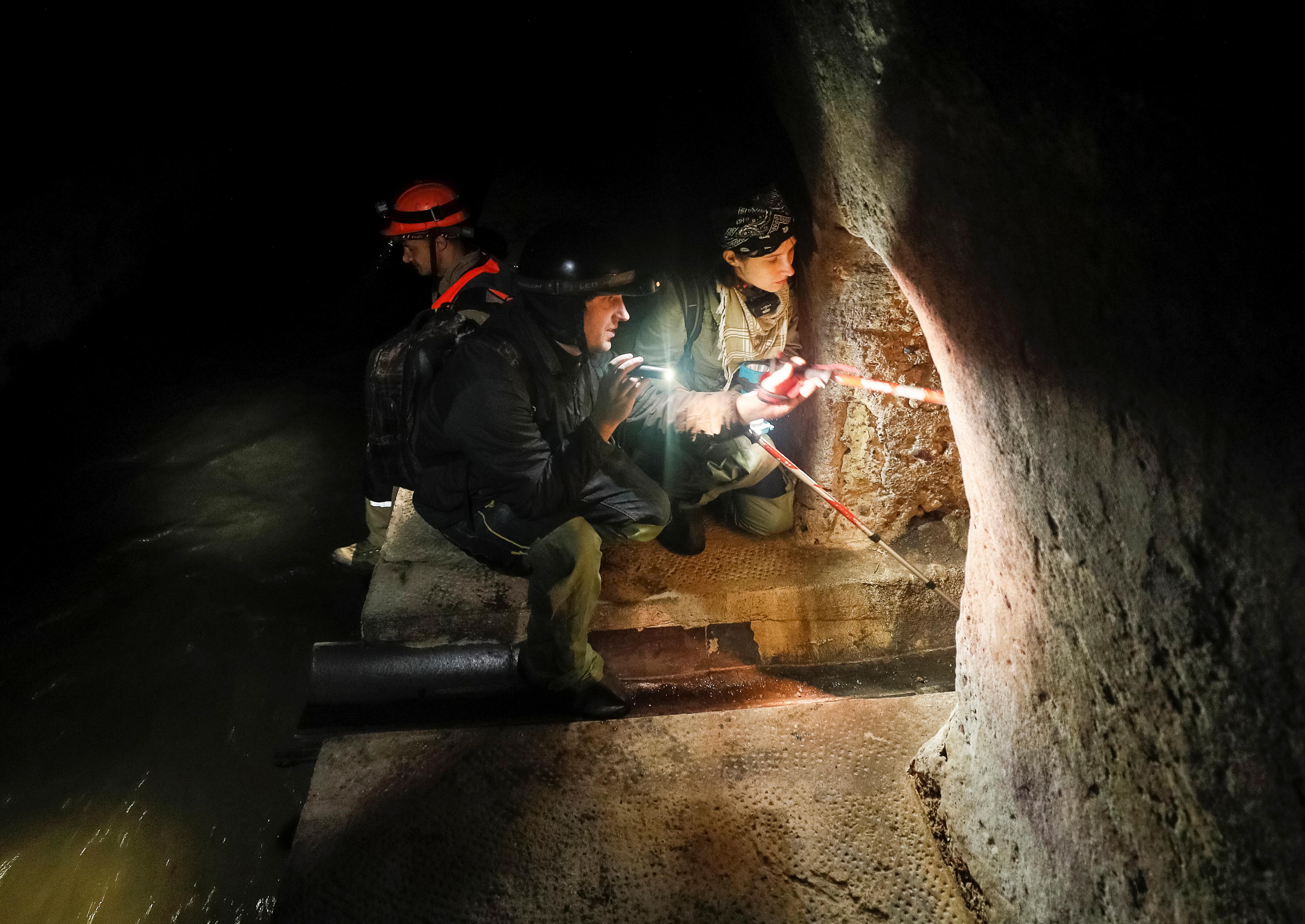 Diggers Andriy Ryshtun and Oleksandr Ivanov and historian Hanna Tychka explore the city sewage system where dozens of Jews were hiding from the Nazis during World War Two in Lviv, Ukraine September 25, 2021. REUTERS/Gleb Garanich