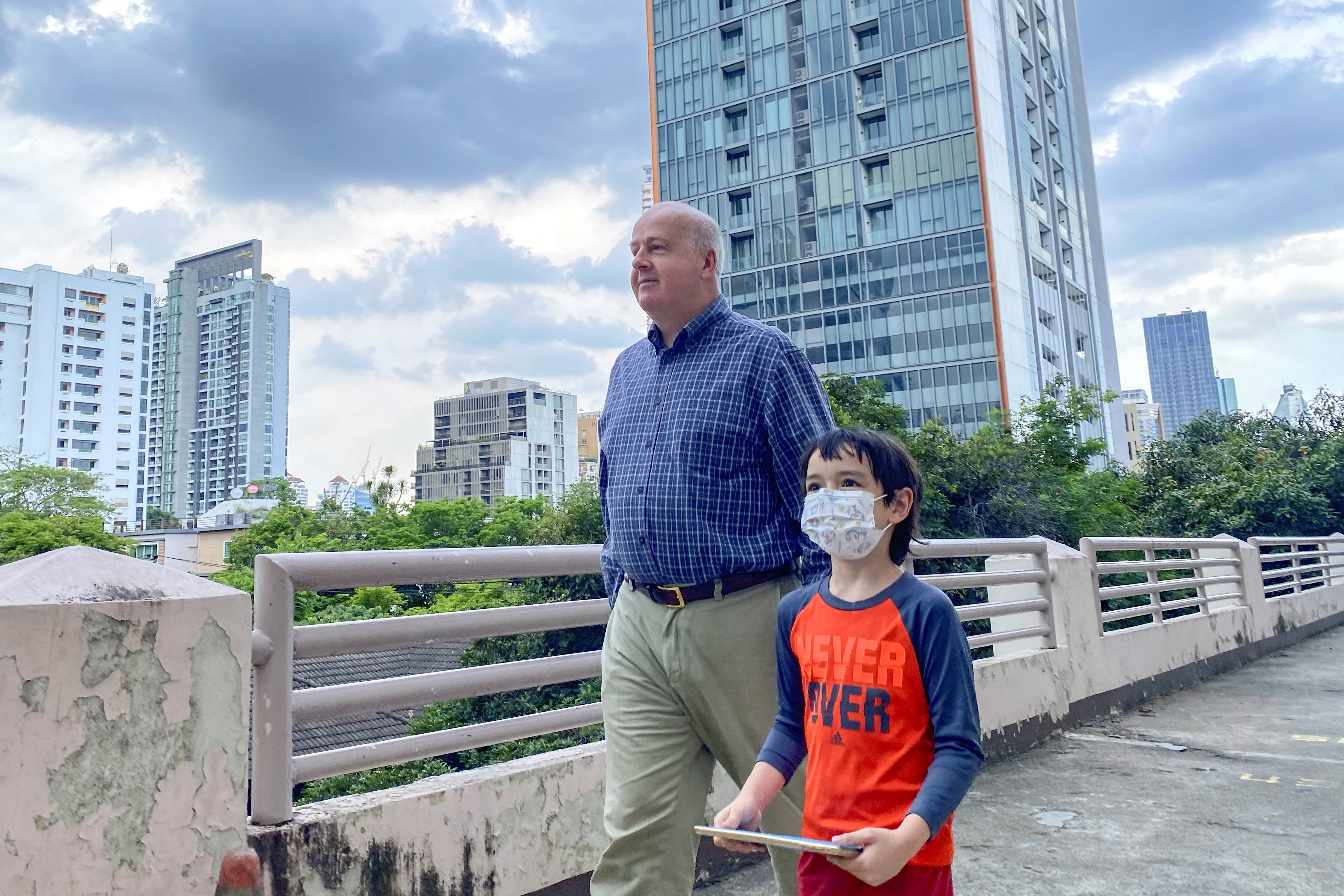 Paul Risley, a U.S. citizen chair of Democrats Abroad, walks with his son during an interview with Reuters in Bangkok, Thailand May 11, 2021.  REUTERS/Jiraporn Kuhakan