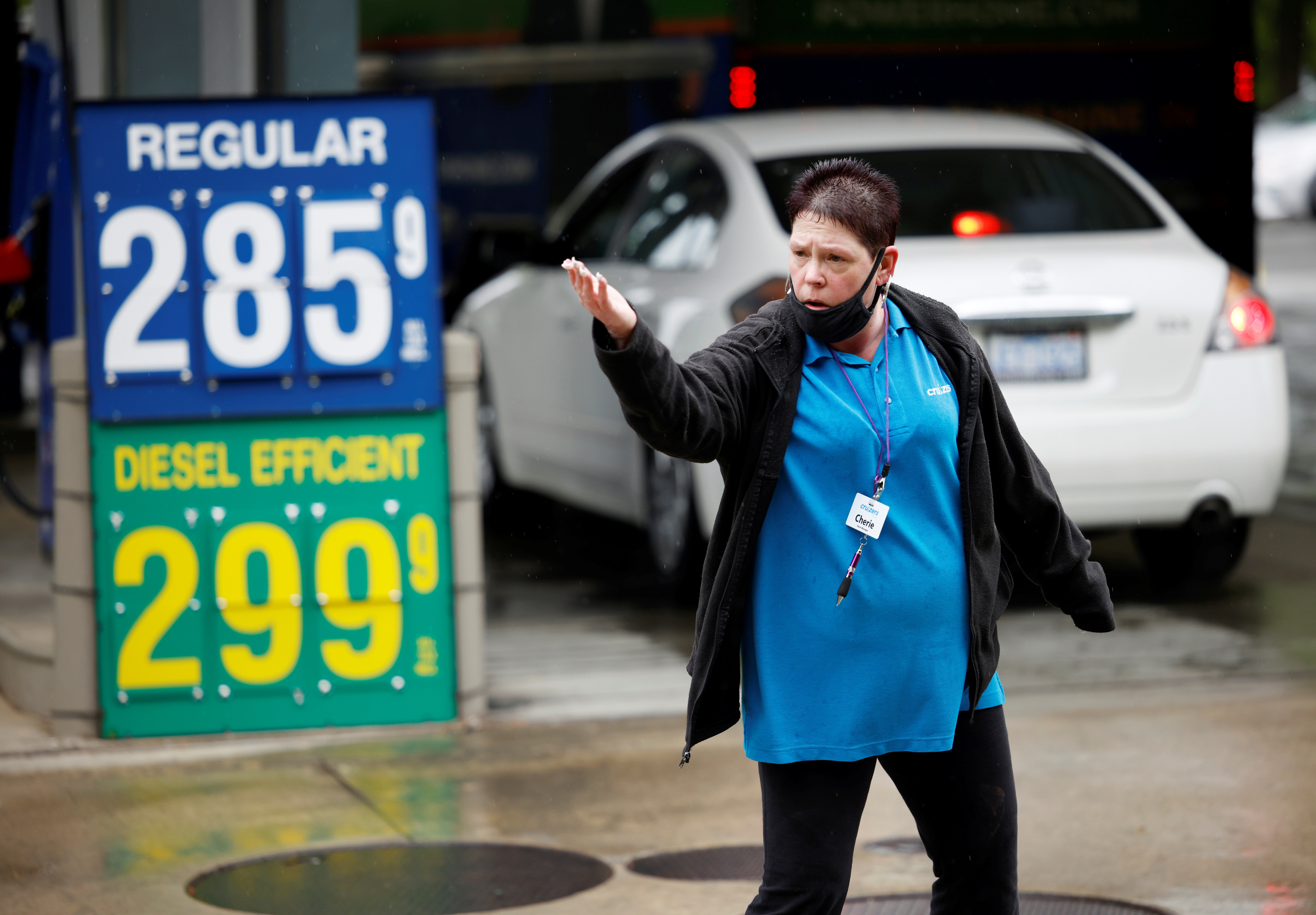 Gasoline station manager Cherie Thomas directs motorists arriving at her outlet after a cyberattack crippled the biggest fuel pipeline in the country, run by Colonial Pipeline, in Chapel Hill, North Carolina, U.S. May 12, 2021.  REUTERS/Jonathan Drake