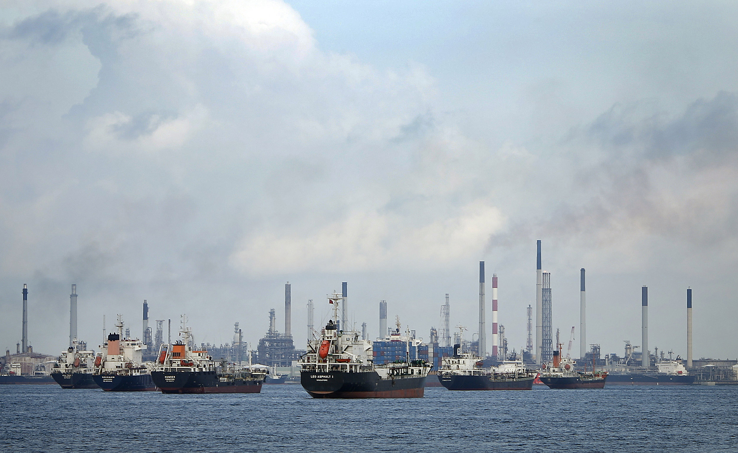 Ships are seen anchored in front of a refinery on Singapore's Bukom Island July 6, 2014. REUTERS/Tim Wimborne