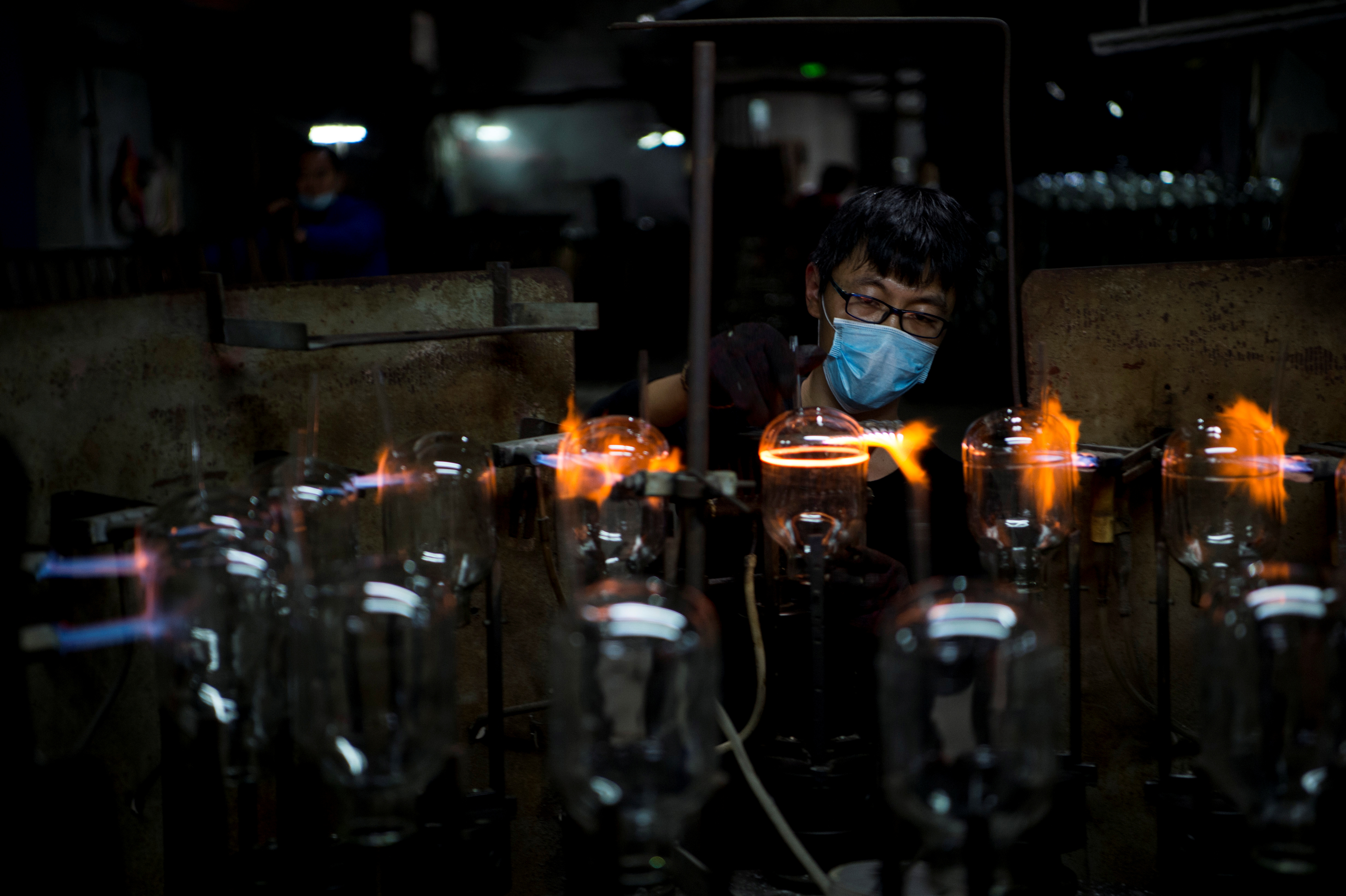 A worker wearing a face mask works on a production line manufacturing glassware products at a factory in Haian, Jiangsu province, China February 29, 2020. Picture taken February 29, 2020. China Daily via REUTERS/File photo