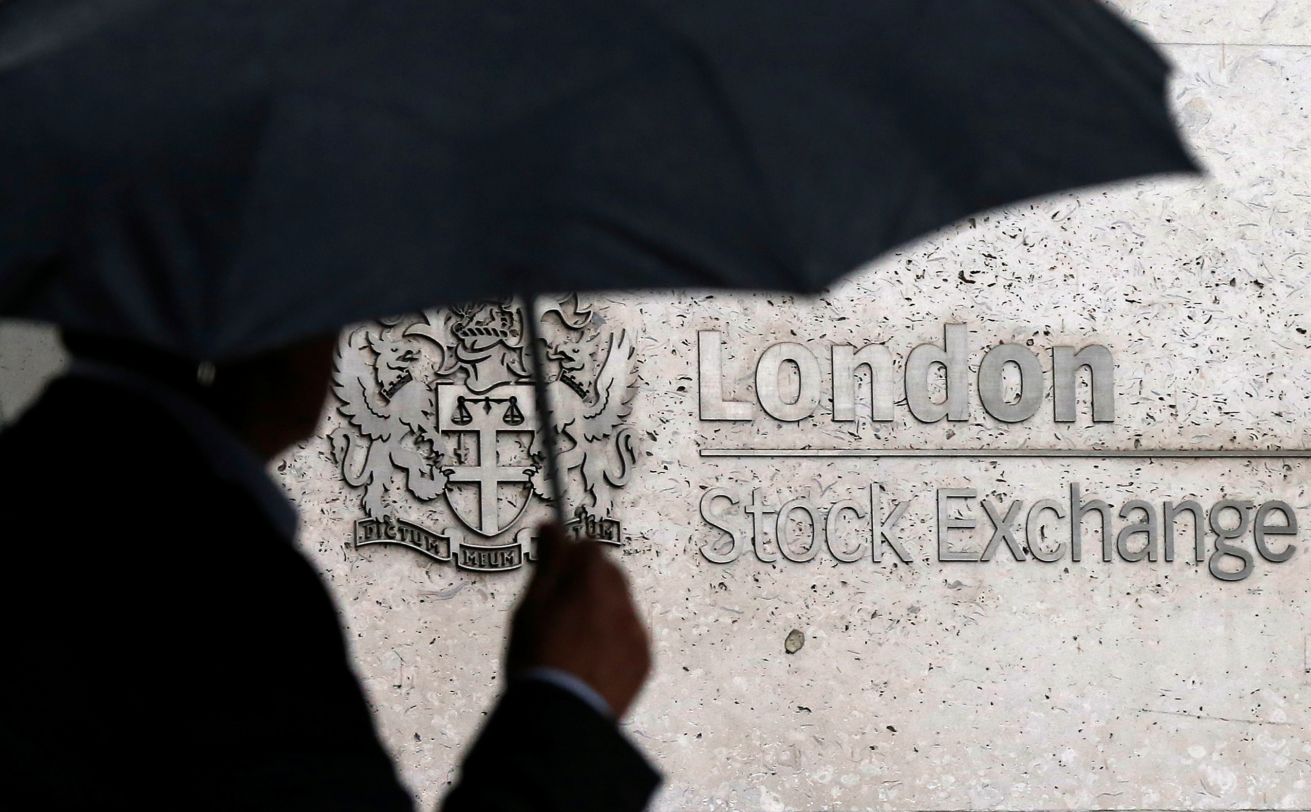 A man shelters under an umbrella as he walks past the London Stock Exchange in London, Britain, August 24, 2015. REUTERS/Suzanne Plunkett/File Photo