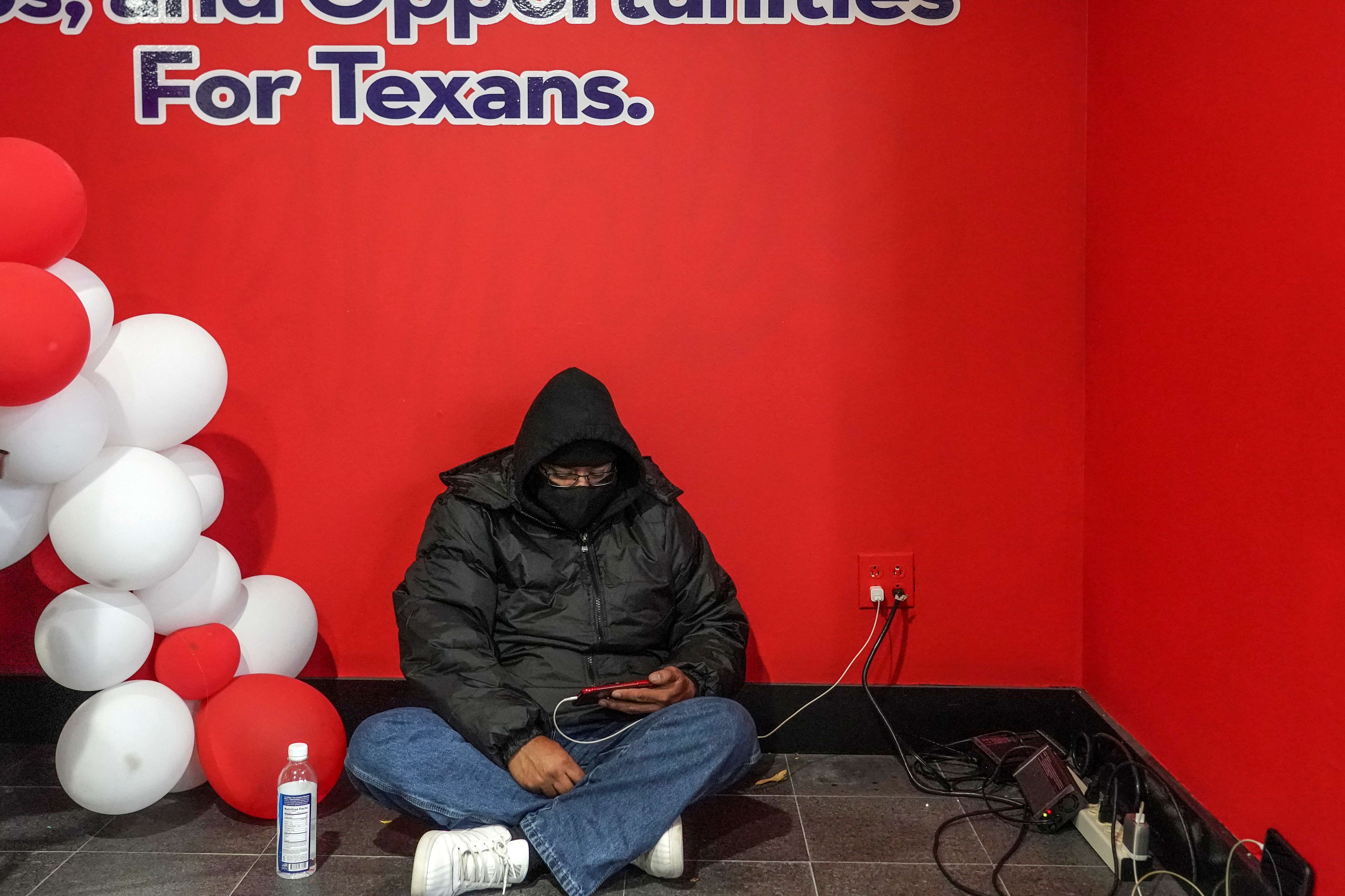 A person charges his smartphone while taking a shelter at Gallery Furniture store which opened its door and transformed into a warming station after winter weather caused electricity blackouts in Houston, Texas, U.S. February 17, 2021.  REUTERS/Go Nakamura